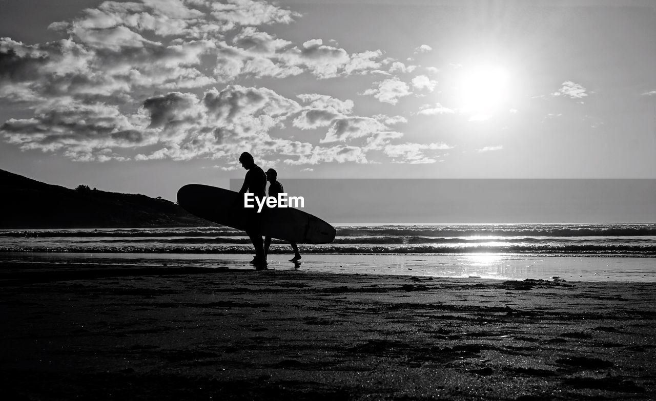 Men With Surfboard Walking On Shore At Beach Against Sky