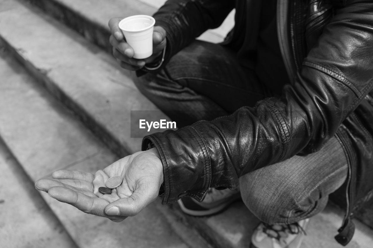 Cropped Image Of Beggar Sitting On Steps