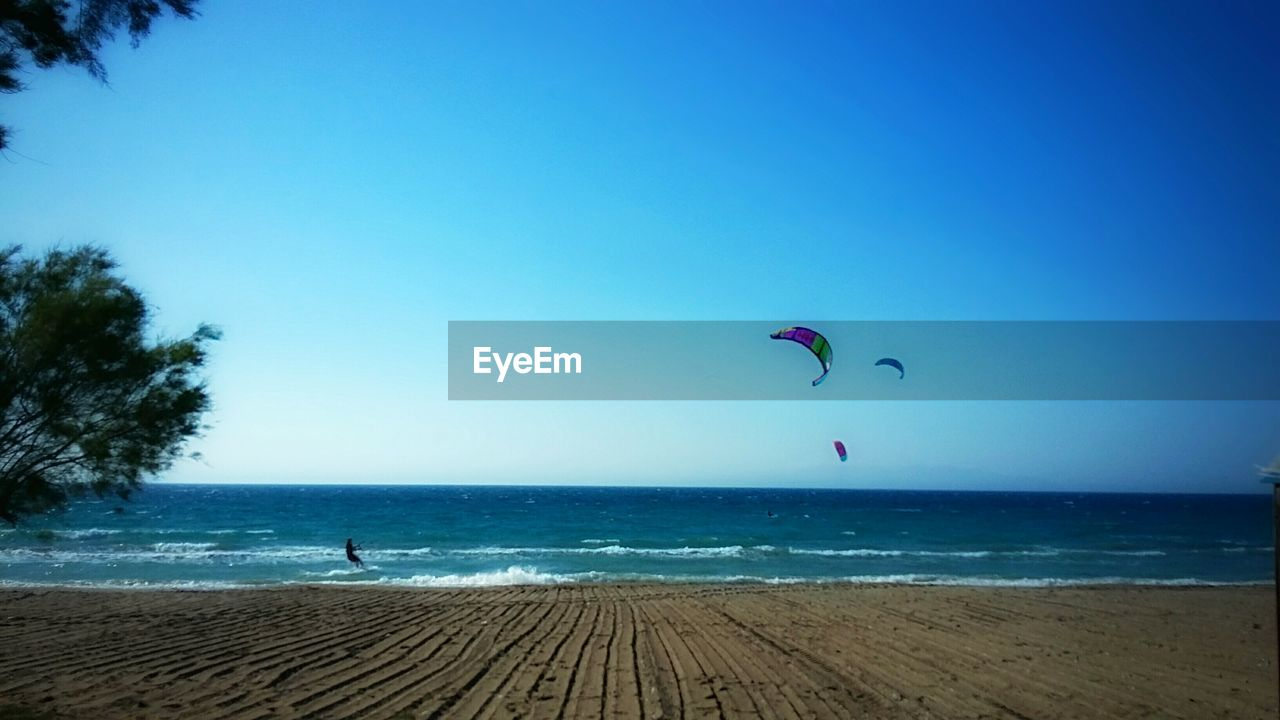 sea, horizon over water, clear sky, one person, nature, real people, leisure activity, blue, beach, water, scenics, day, beauty in nature, tranquil scene, outdoors, sky, lifestyles, adventure, vacations, tranquility, tree, men, flying, extreme sports, parachute, paragliding, people