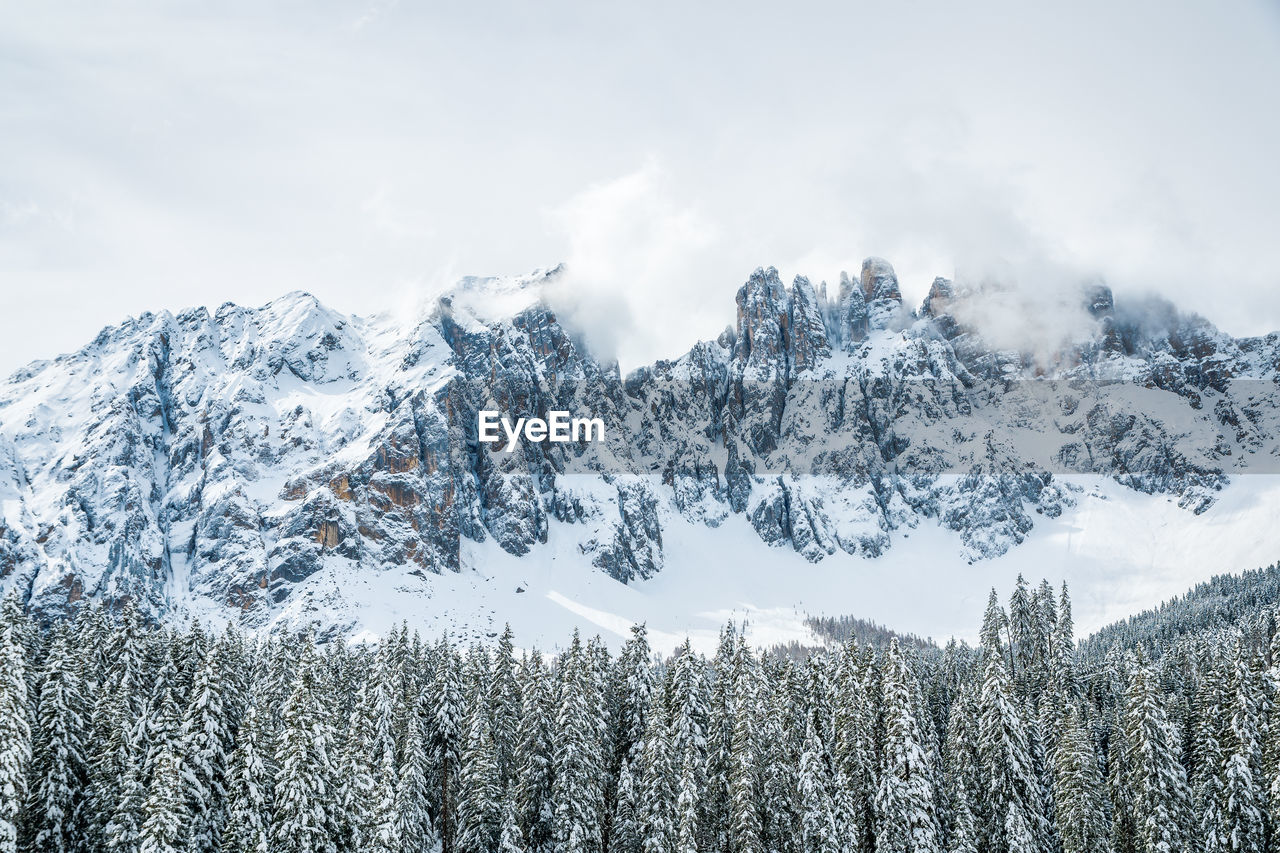 winter, cold temperature, beauty in nature, snow, tree, tranquil scene, scenics - nature, tranquility, plant, sky, cloud - sky, mountain, non-urban scene, environment, nature, no people, white color, day, forest, snowcapped mountain, woodland, coniferous tree, mountain peak