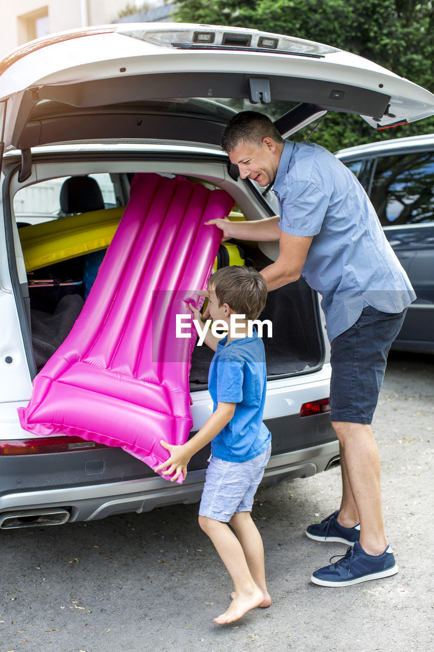 Full length of father with son preparing for picnic by car