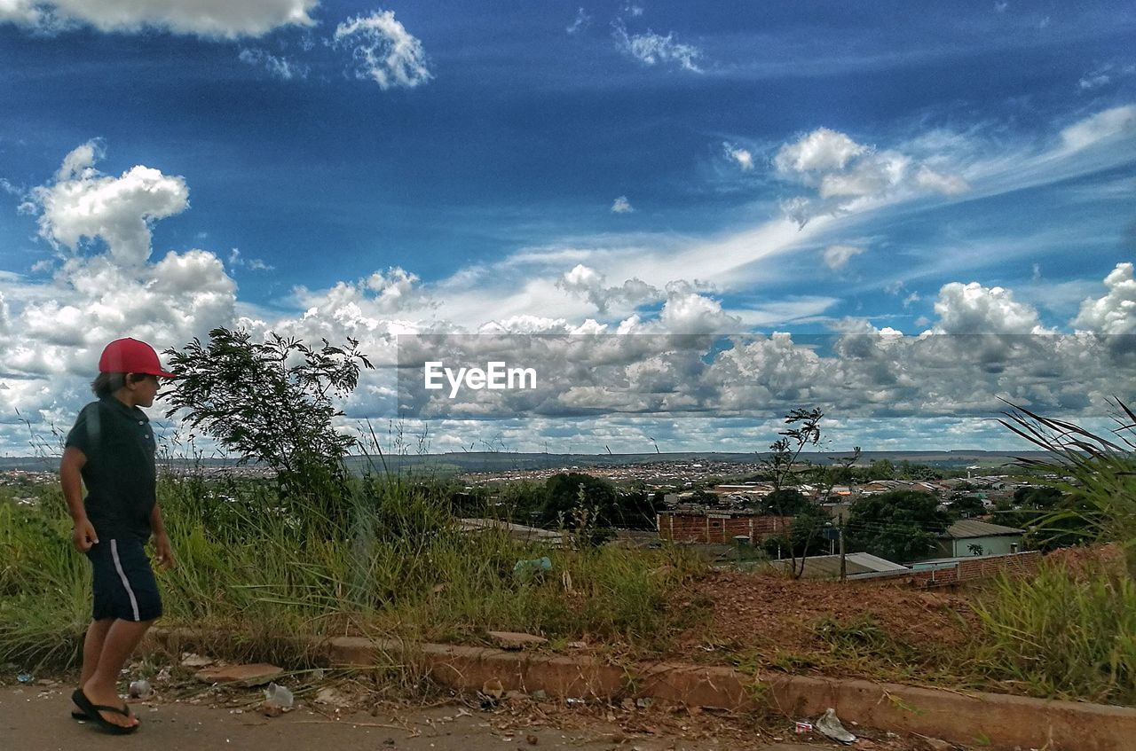 sky, cloud - sky, one person, real people, plant, standing, nature, rear view, day, full length, beauty in nature, land, scenics - nature, casual clothing, leisure activity, lifestyles, outdoors, tree, men, looking at view