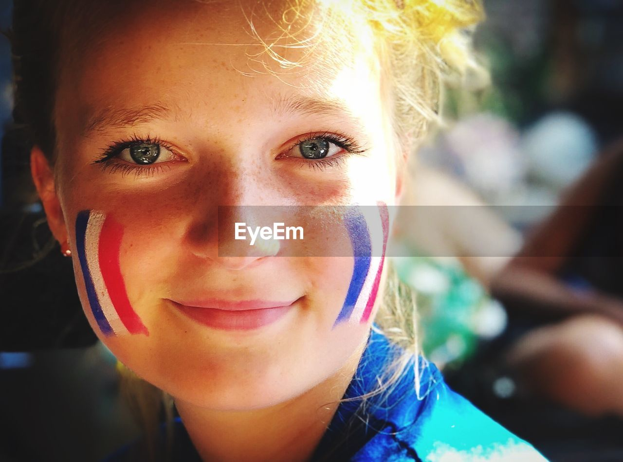 Close-Up Portrait Of Girl With French Flag Face Paint
