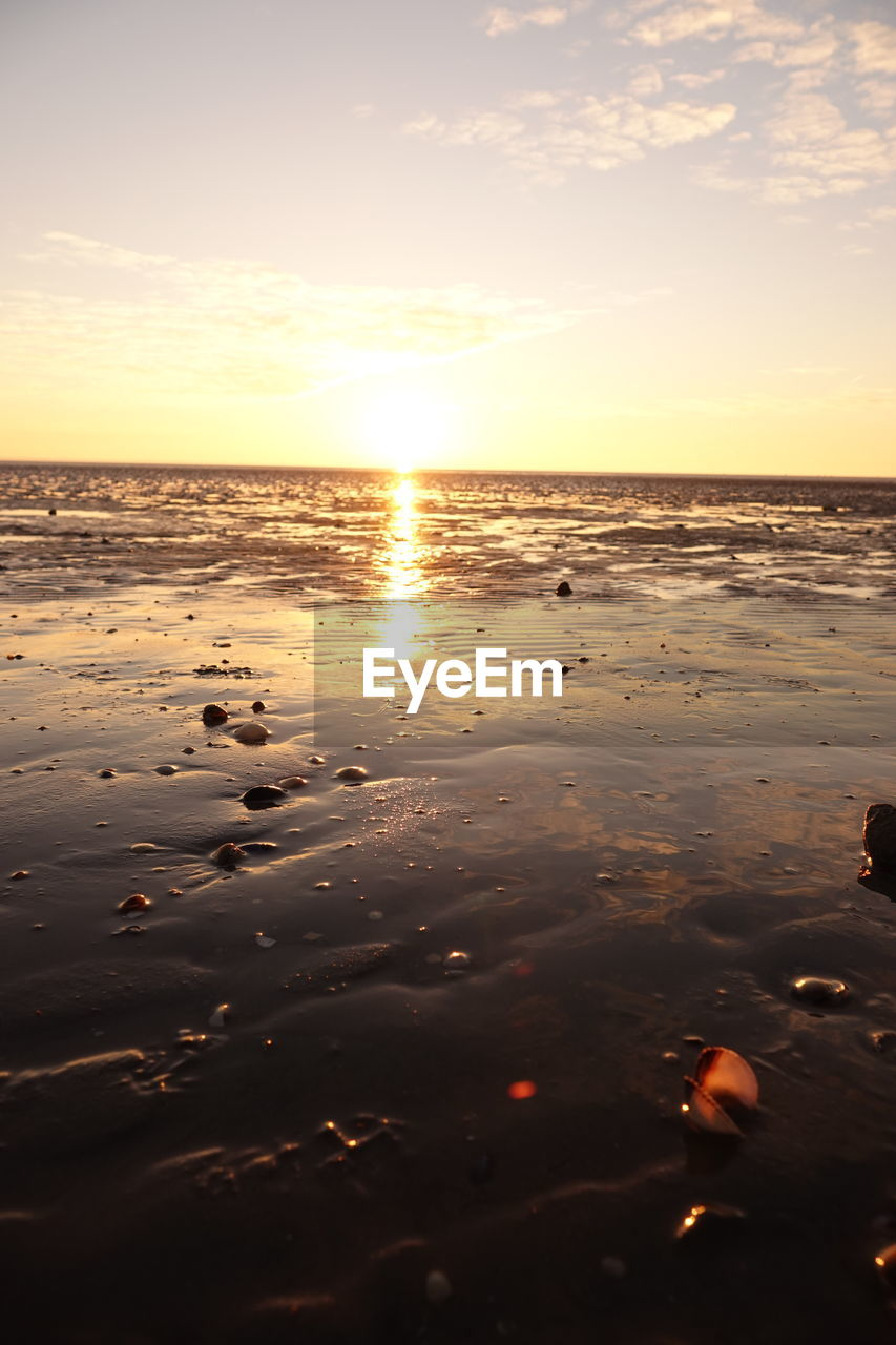 sky, sunset, water, beauty in nature, scenics - nature, sea, tranquility, tranquil scene, reflection, land, beach, cloud - sky, sunlight, orange color, sun, horizon, horizon over water, nature, no people, outdoors, lens flare, surface level