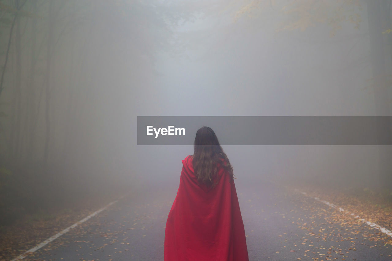 Rear View Of Woman Standing On Road In Foggy Weather