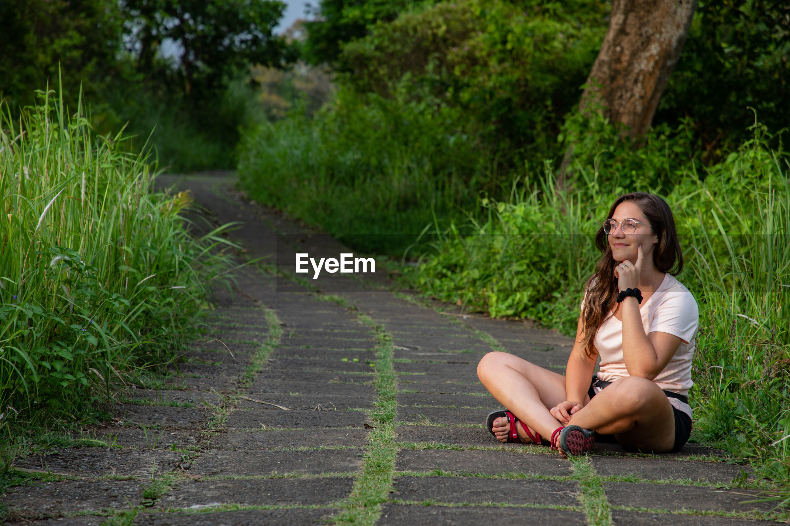 Smiling woman sitting on footpath amidst grass