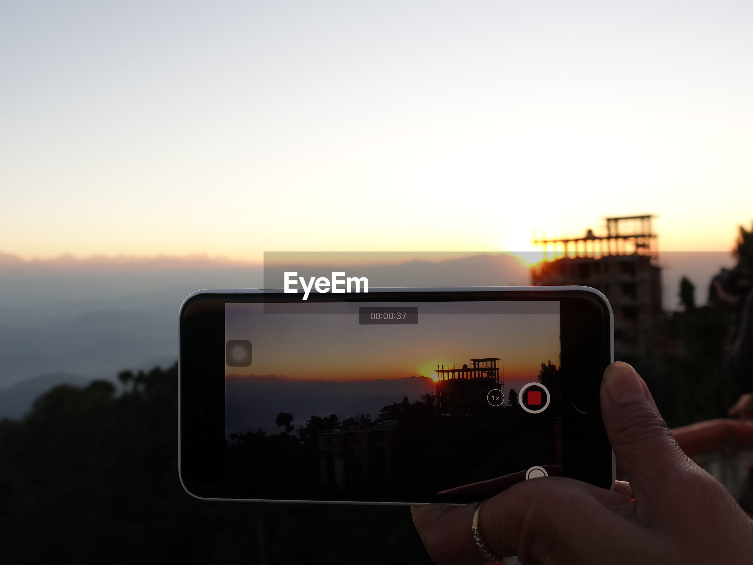 MAN PHOTOGRAPHING USING SMART PHONE AGAINST SKY