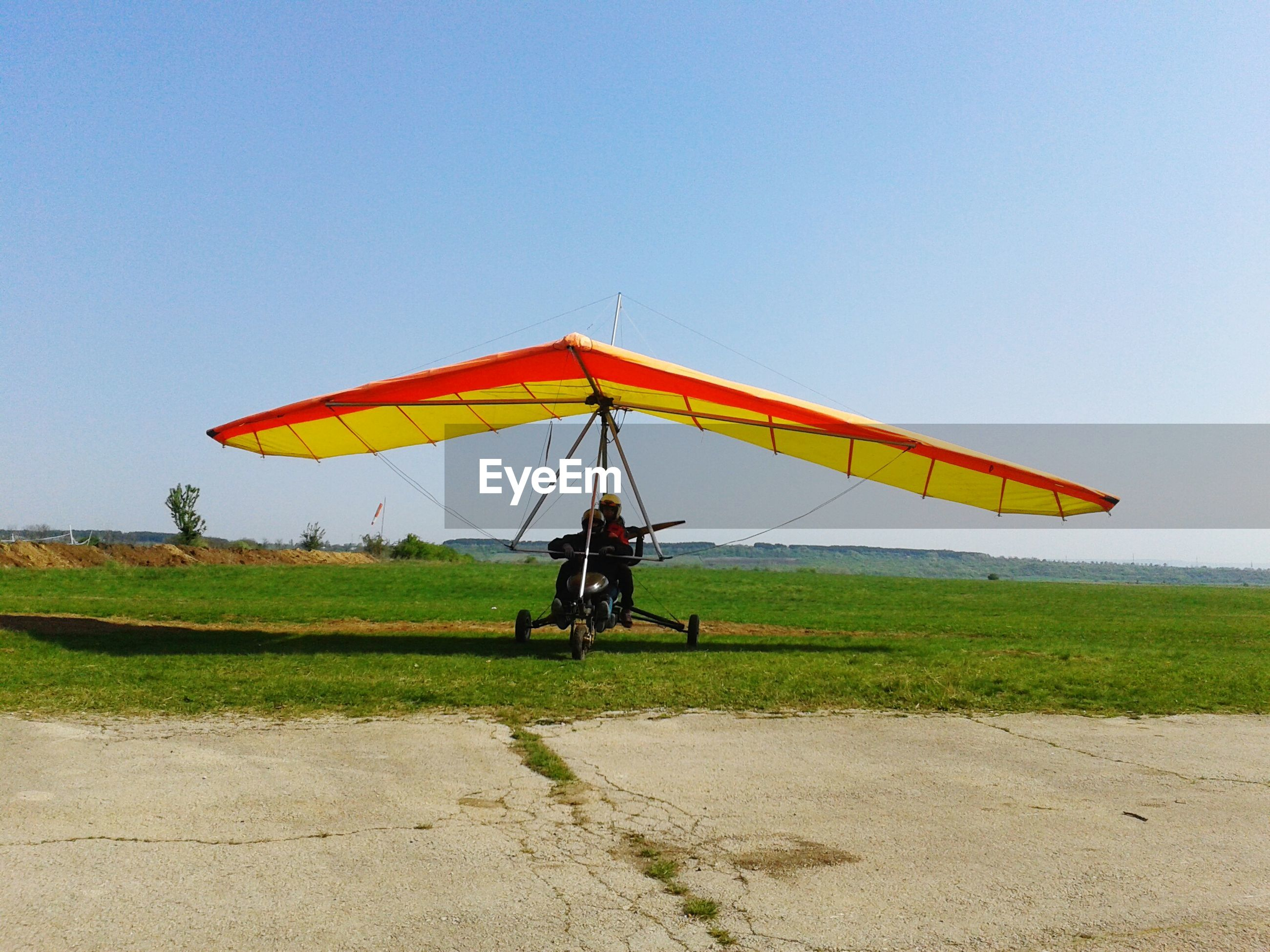 transportation, clear sky, field, grass, mode of transport, copy space, landscape, leisure activity, lifestyles, mid-air, sky, travel, full length, blue, childhood, outdoors, nature, tranquility