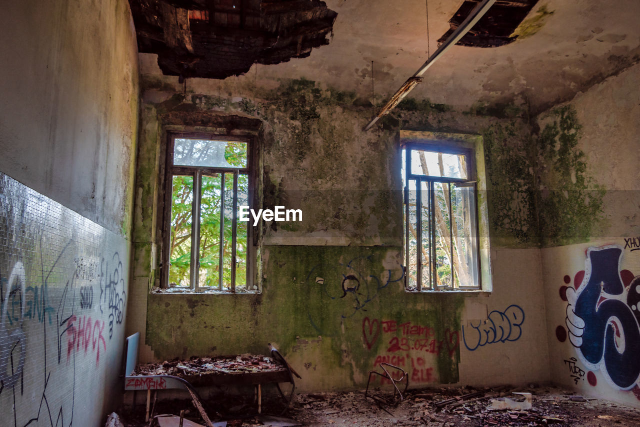 window, abandoned, indoors, damaged, no people, obsolete, decline, day, deterioration, run-down, messy, graffiti, architecture, bad condition, home interior, old, building, house, destruction, ruined, ceiling