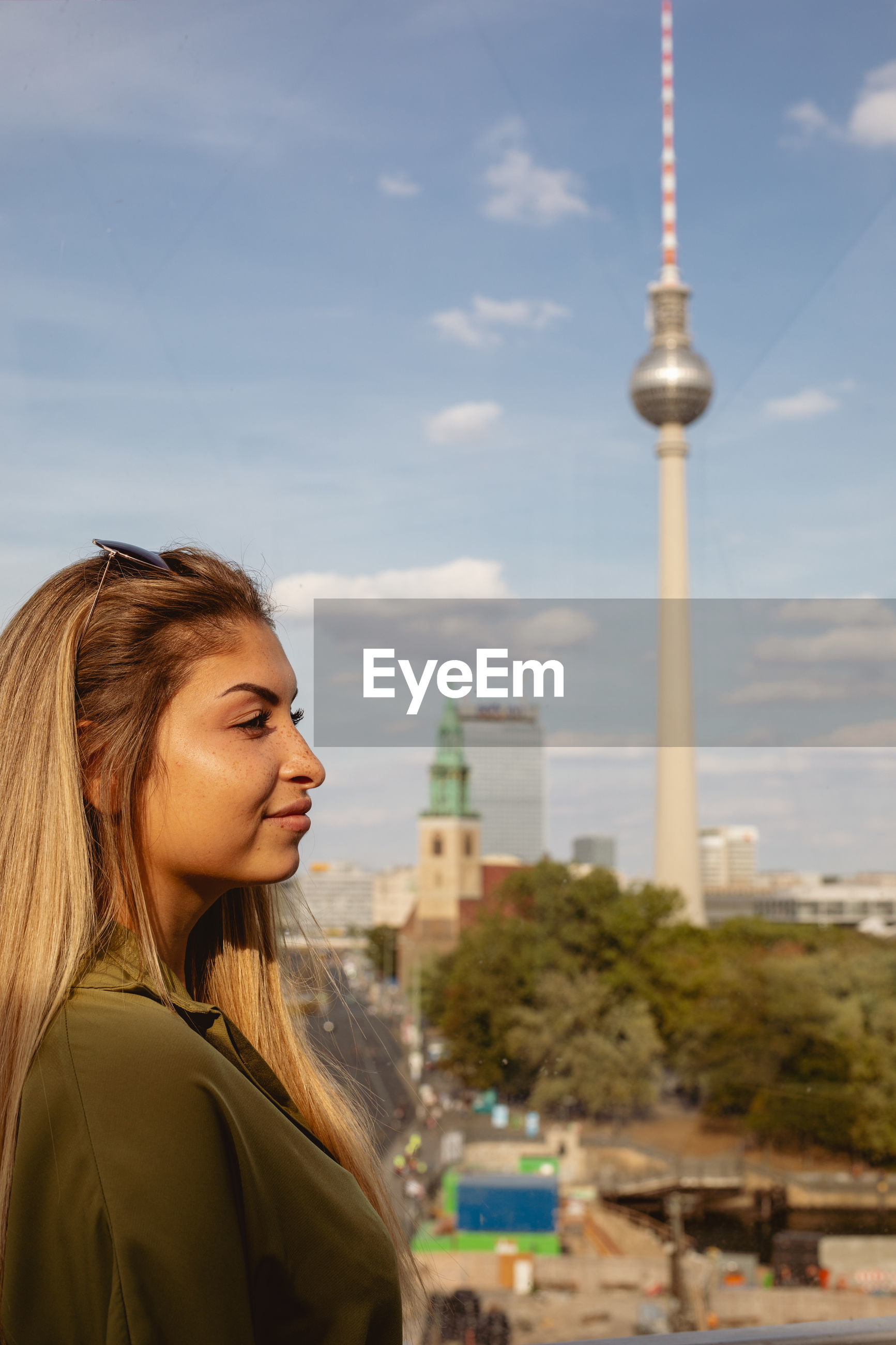 Woman looking away against fernsehturm in city