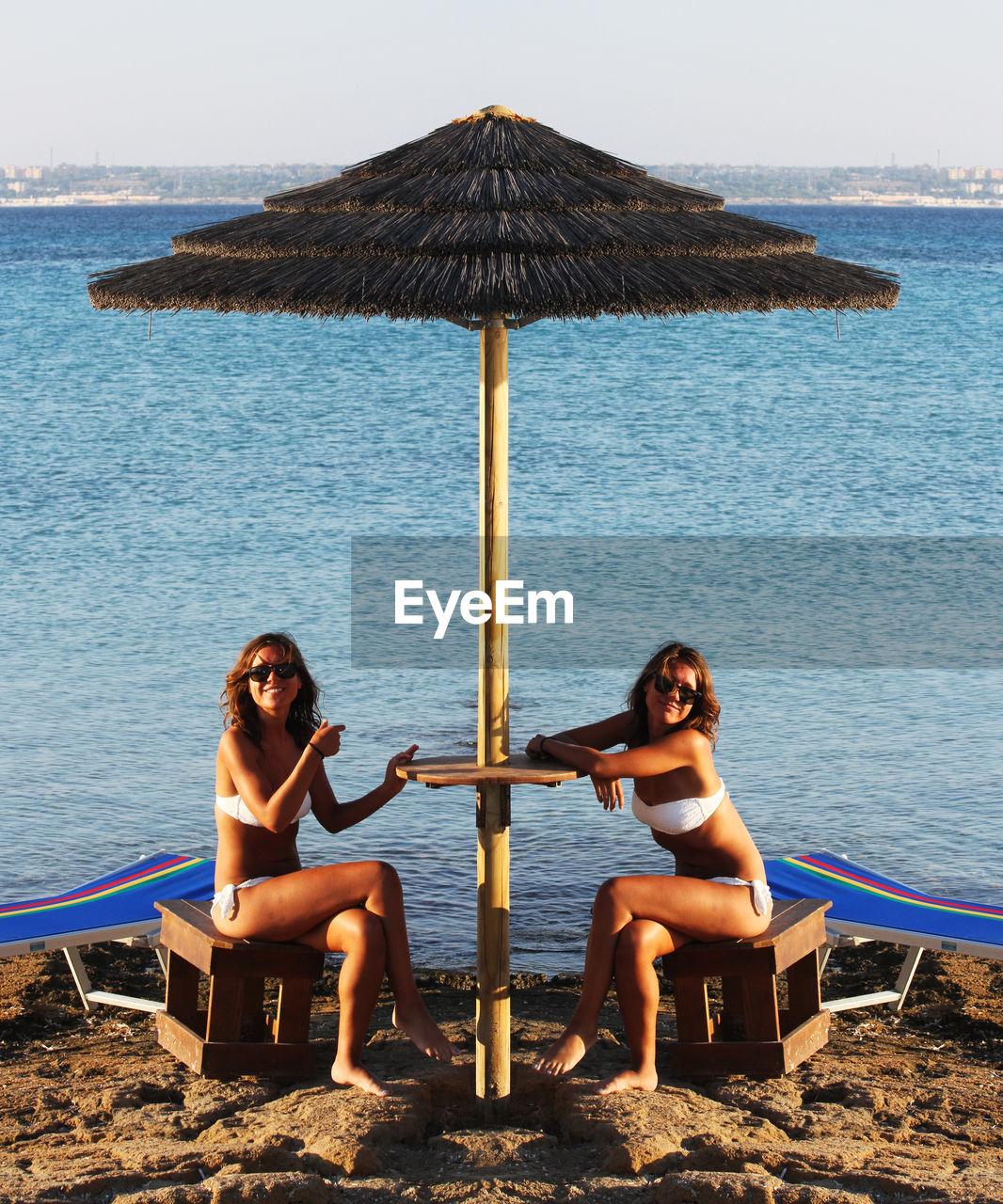 Multiple Image Of Woman Wearing Bikini While Sitting On Rocky Shore
