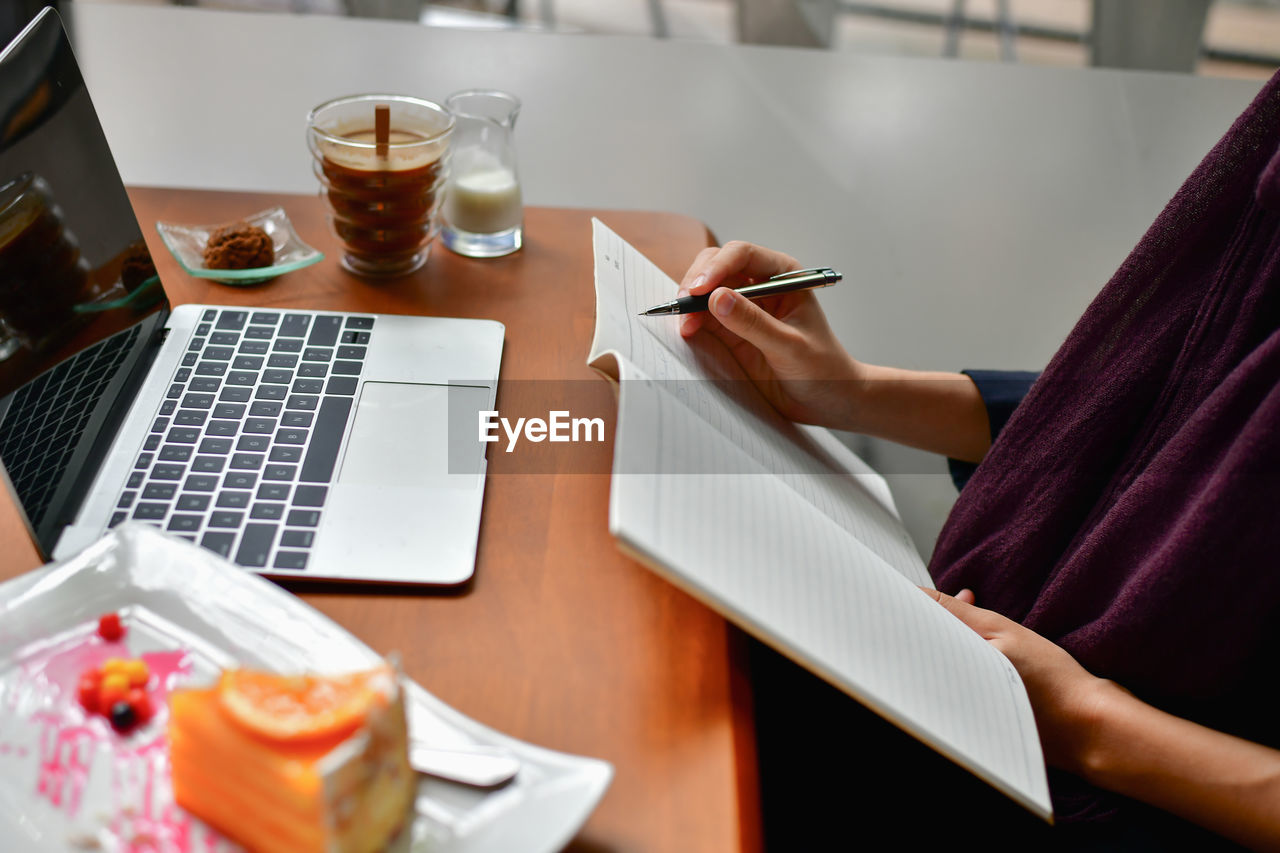 laptop, wireless technology, table, technology, one person, computer, real people, connection, communication, pen, adult, lifestyles, using laptop, indoors, human hand, midsection, women, drink, portable information device, hand, glass