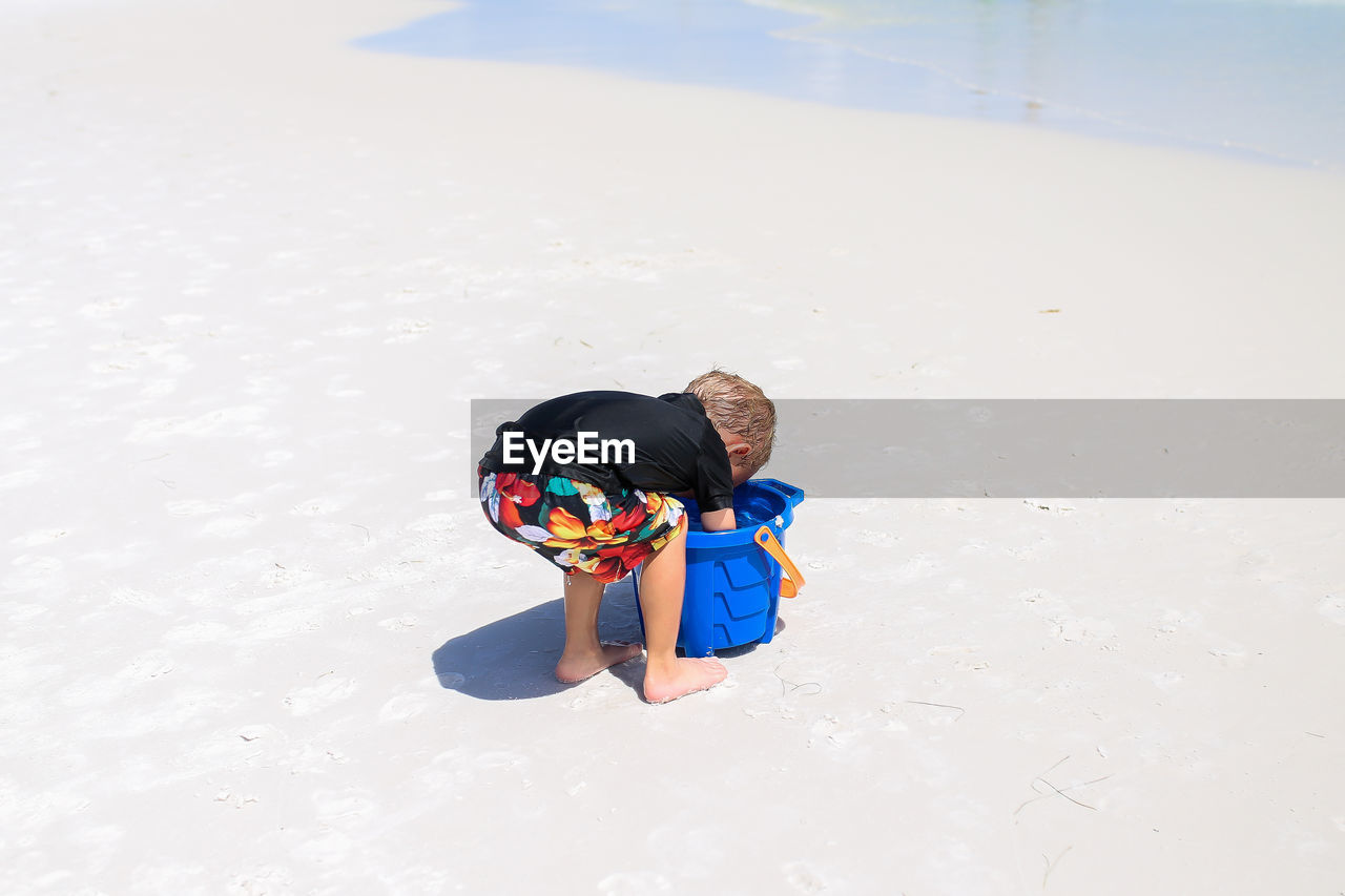 Boy searching in bucket at beach