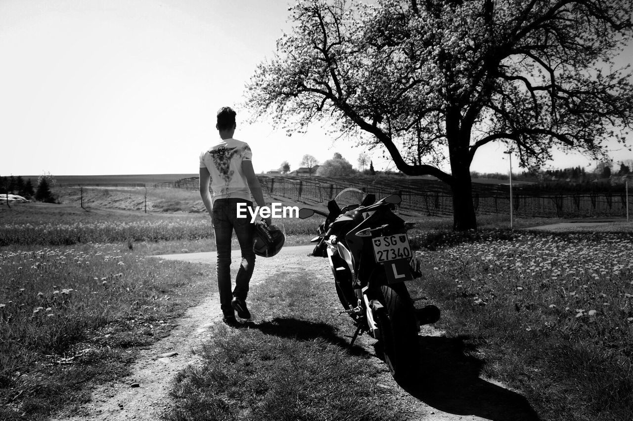 full length, field, tree, togetherness, grass, day, real people, two people, riding, leisure activity, front view, bicycle, casual clothing, nature, landscape, outdoors, boys, growth, bonding, clear sky, sky, men, friendship, young adult, people