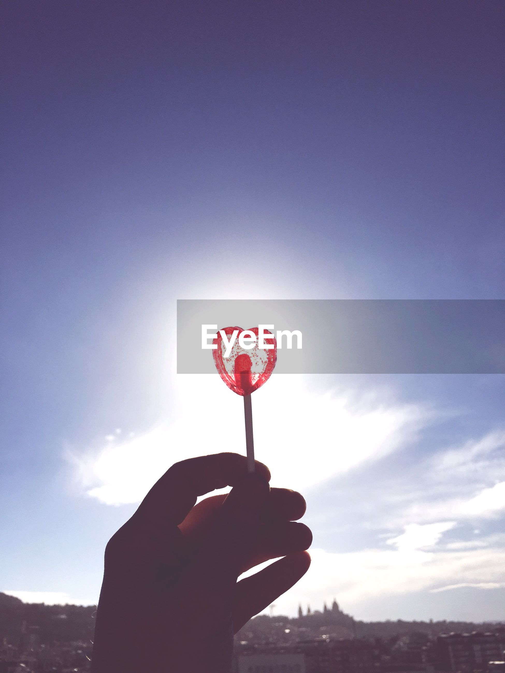 Cropped image of hand holding ring against clear sky