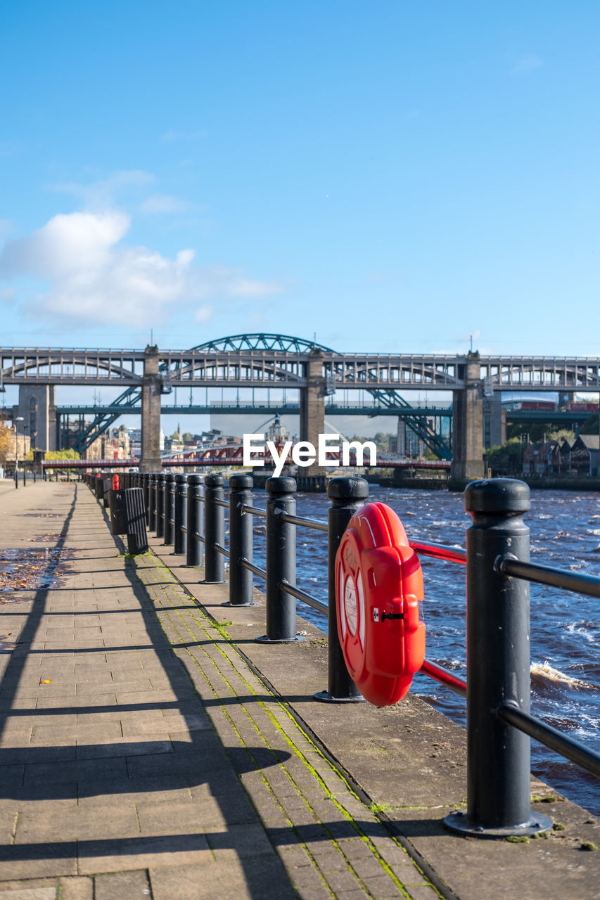 sky, water, built structure, red, transportation, nature, architecture, connection, river, bridge, day, bridge - man made structure, railing, sunlight, outdoors, blue, no people, mode of transportation, pier