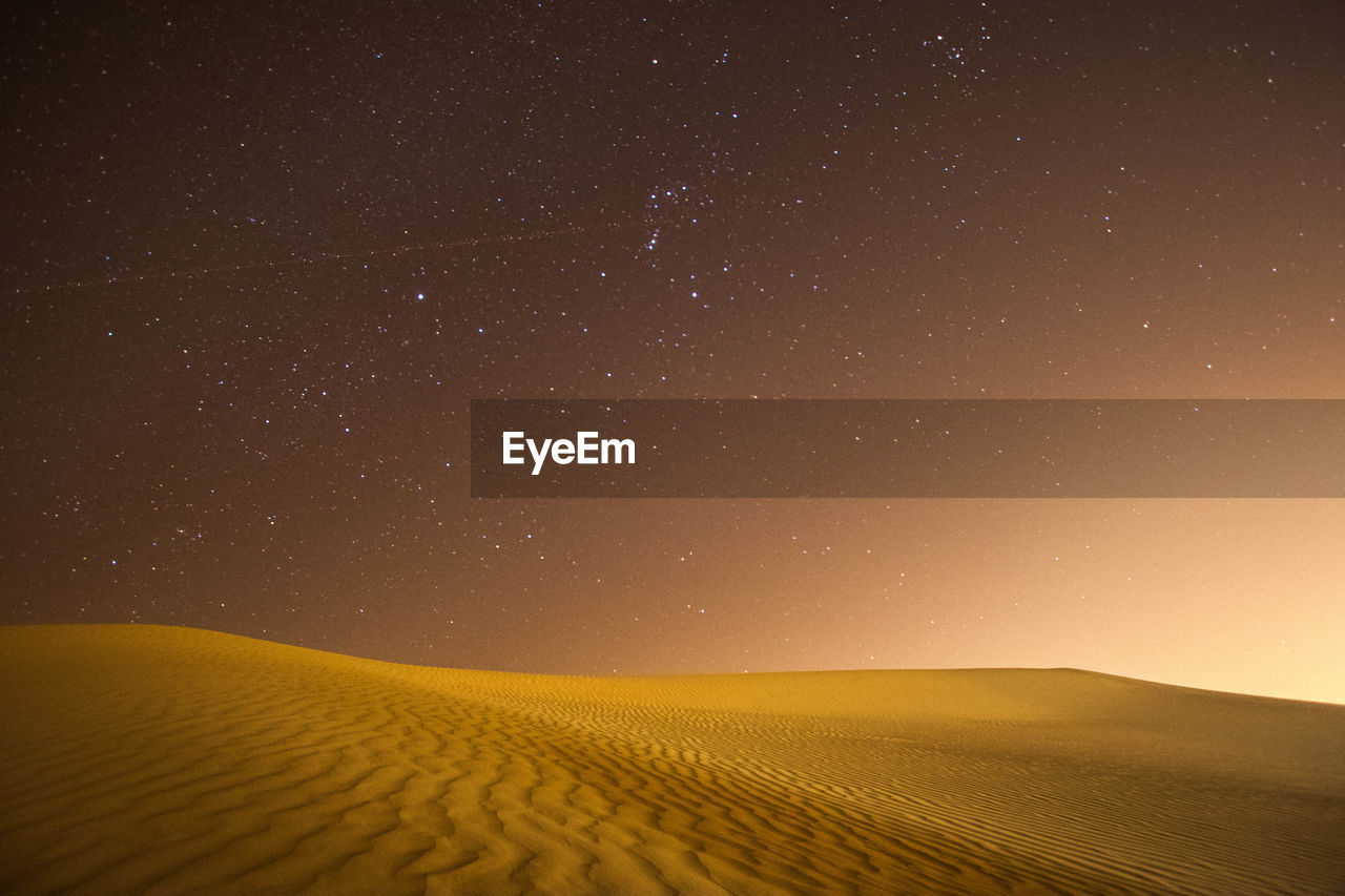 Scenic View Of Desert Against Star Field In Sky At Night