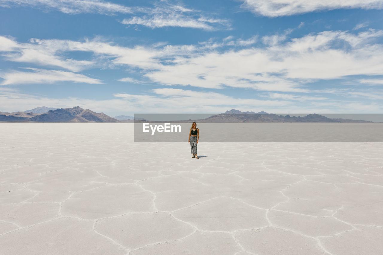 MAN STANDING ON DESERT AGAINST MOUNTAIN