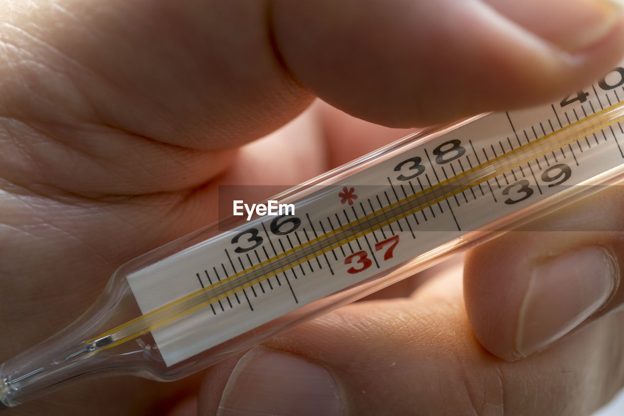Close-up of human hand holding thermometer