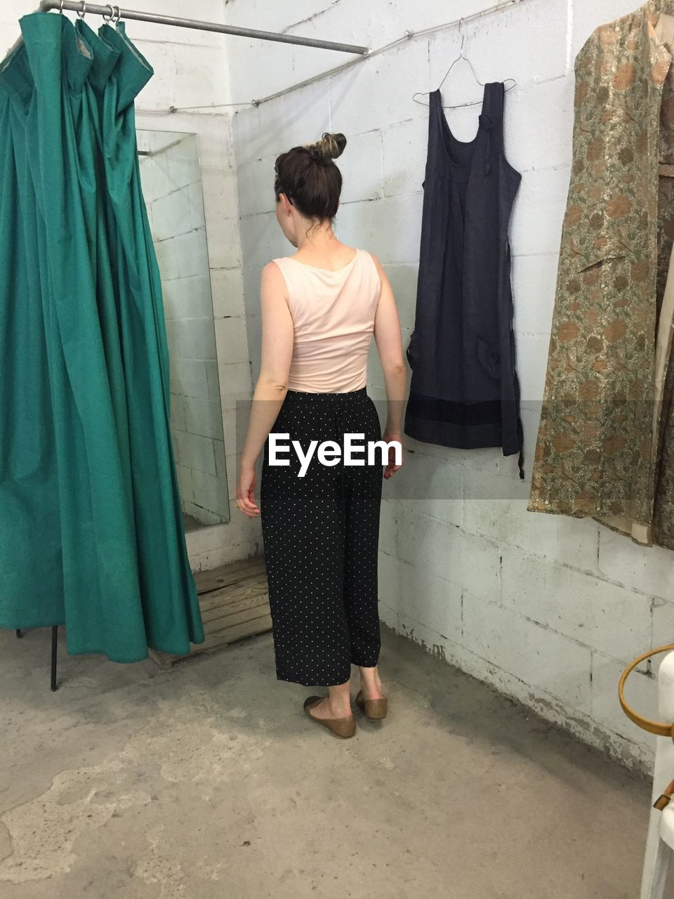fashion, standing, one person, clothing, real people, indoors, clothing store, rear view, retail, coathanger, fitting room, store, full length, choice, lifestyles, women, day, young adult, young women, bride, adult, people