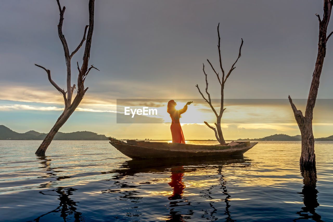 Woman standing in boat on sea during sunset