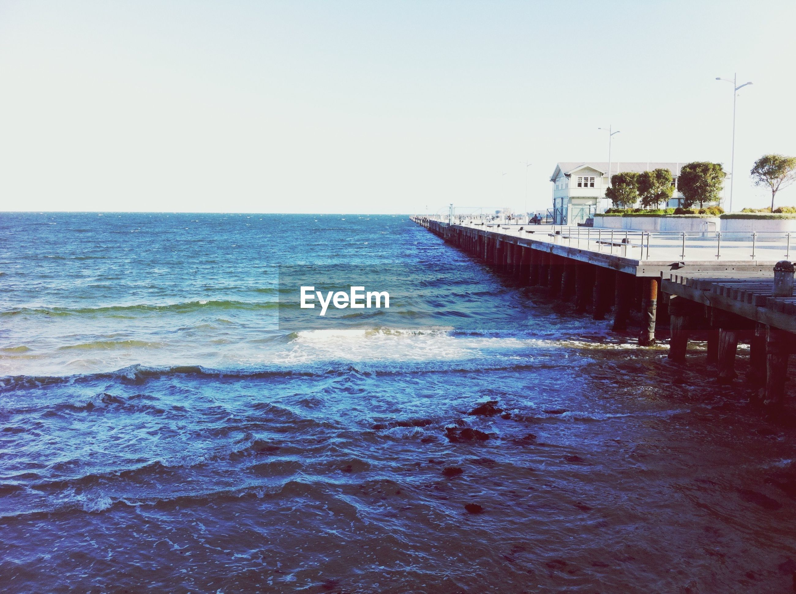 water, sea, horizon over water, clear sky, beach, copy space, pier, tranquil scene, tranquility, wave, scenics, built structure, shore, nature, sky, waterfront, beauty in nature, blue, rippled, architecture