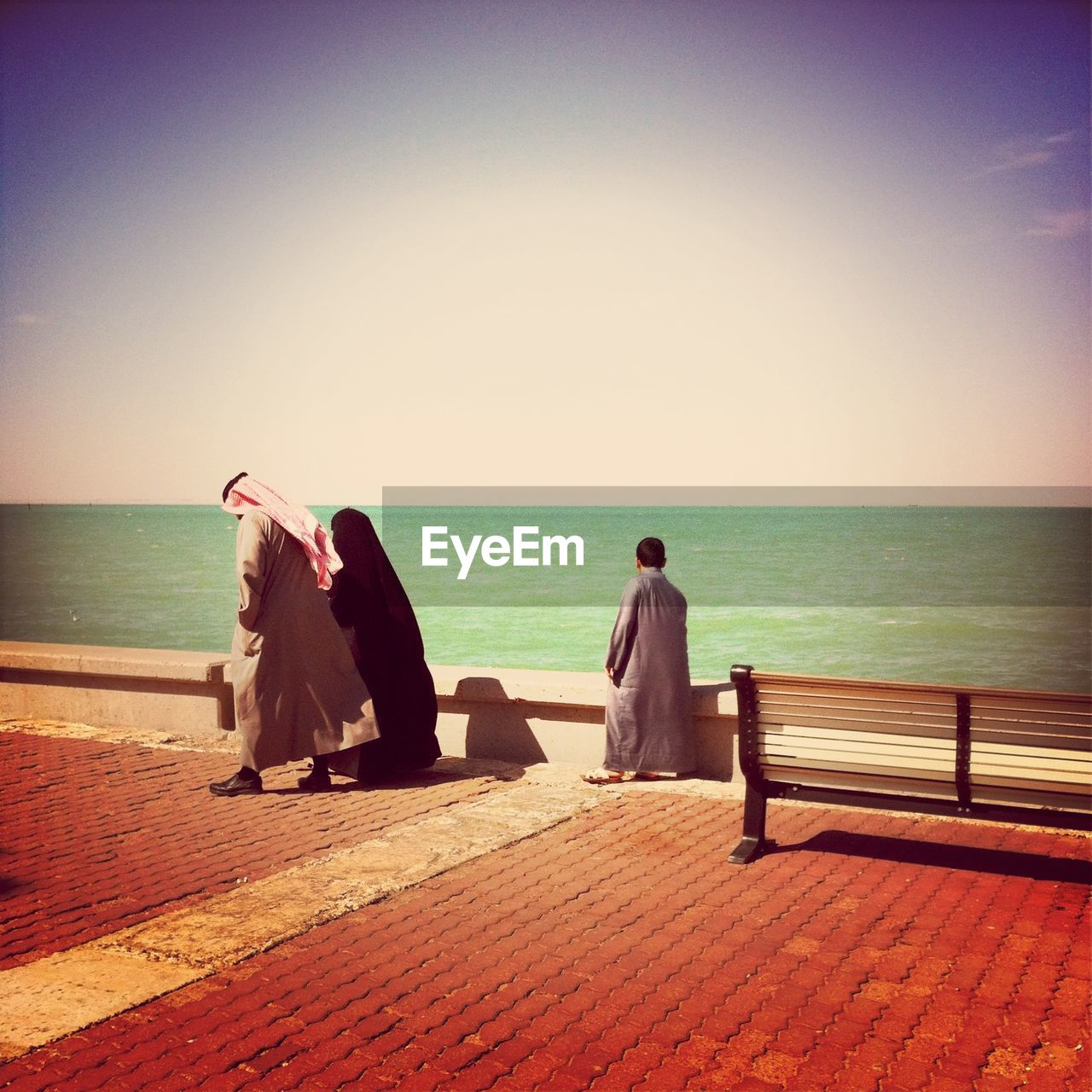 Arab family walking on cobbled lane against the sea