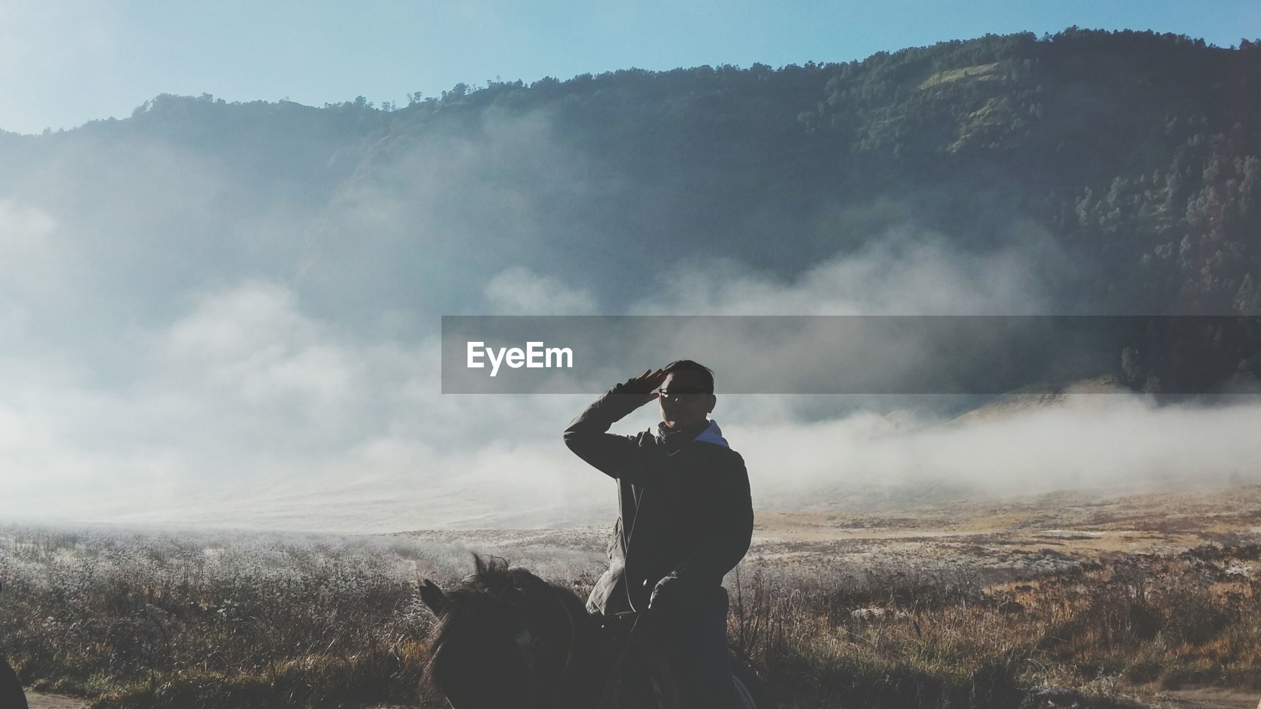 Man saluting while sitting on horse against mountains during foggy weather