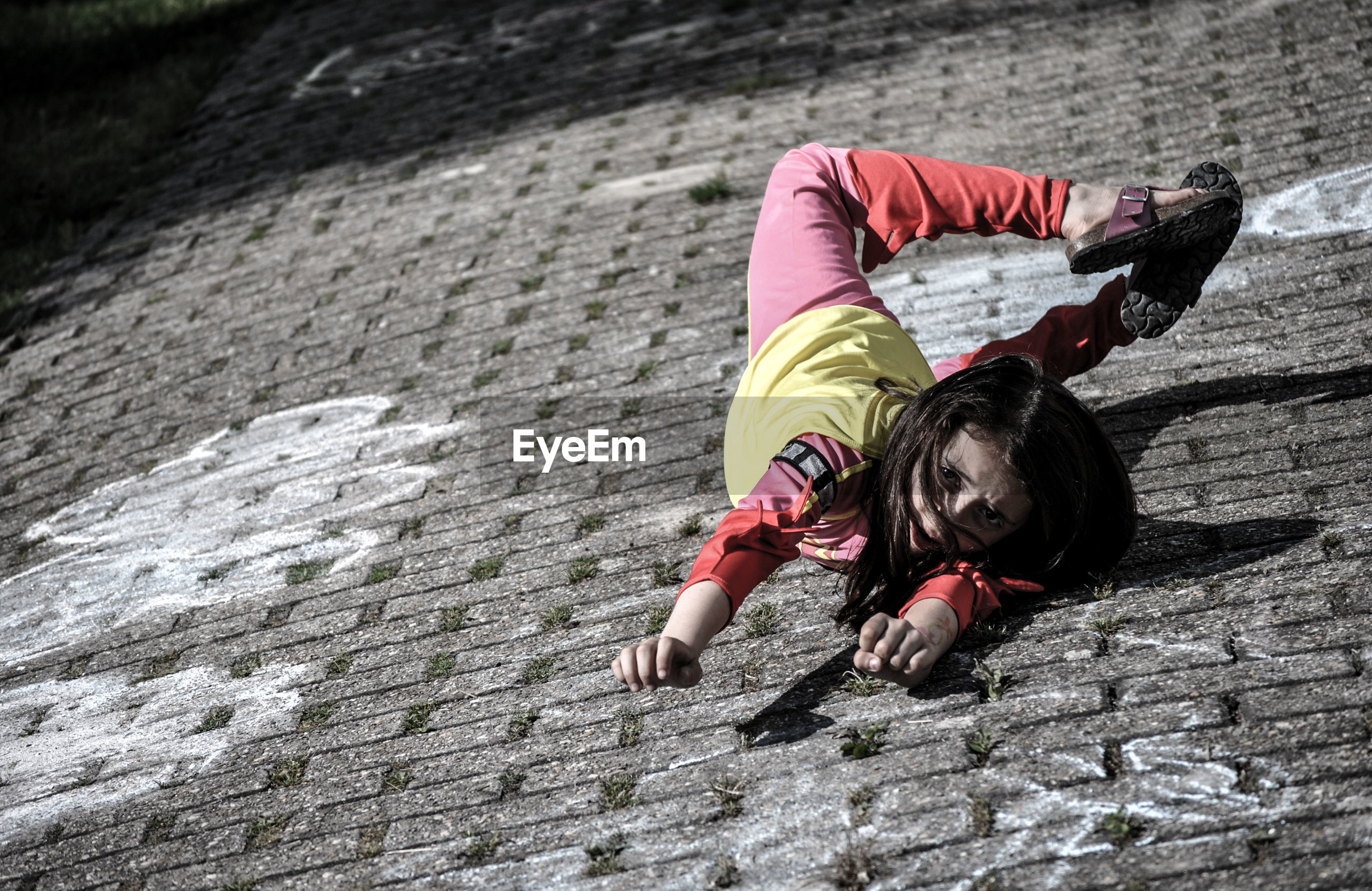 Portrait of girl falling on street
