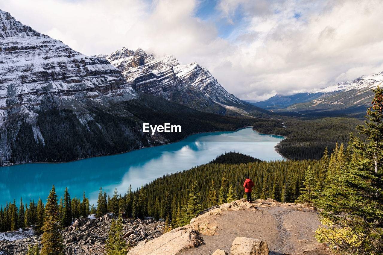 High angle view of woman standing on mountain by lake against sky