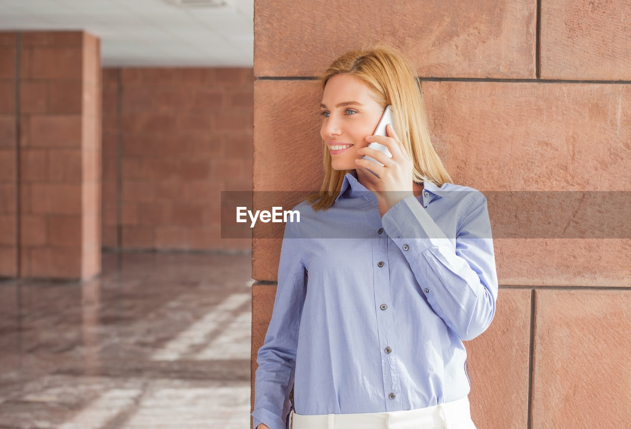 Close-Up Of Businesswoman Talking On Phone While Standing On Floor