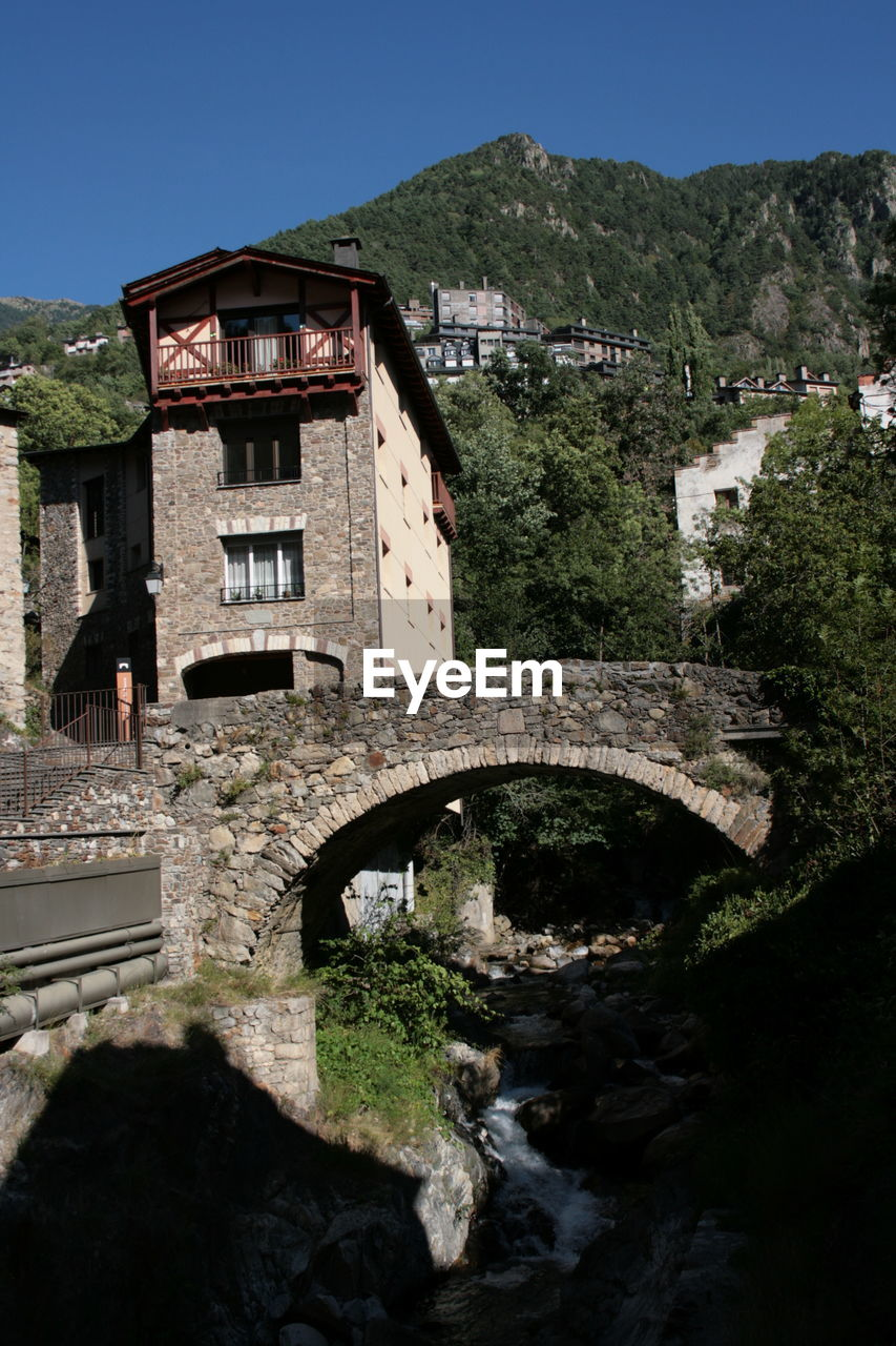 architecture, bridge - man made structure, built structure, connection, arch, tree, day, outdoors, no people, bridge, building exterior, clear sky, mountain, nature, water, sky