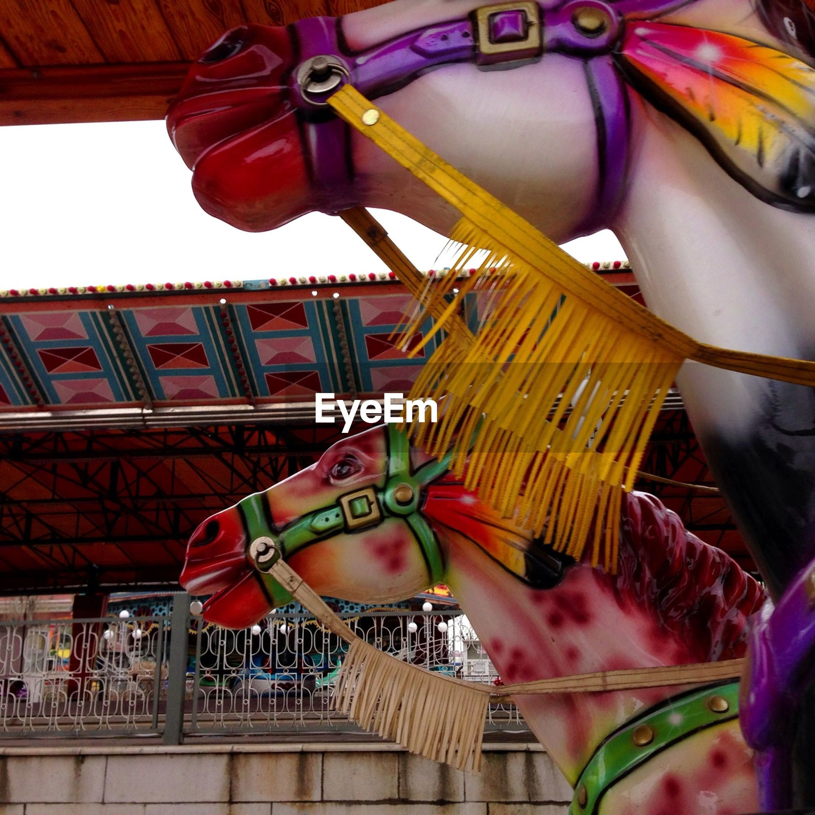 low angle view, architecture, built structure, amusement park, hanging, building exterior, arts culture and entertainment, tradition, cultures, amusement park ride, art and craft, carousel, art, decoration, day, multi colored, outdoors, sculpture, temple - building, creativity