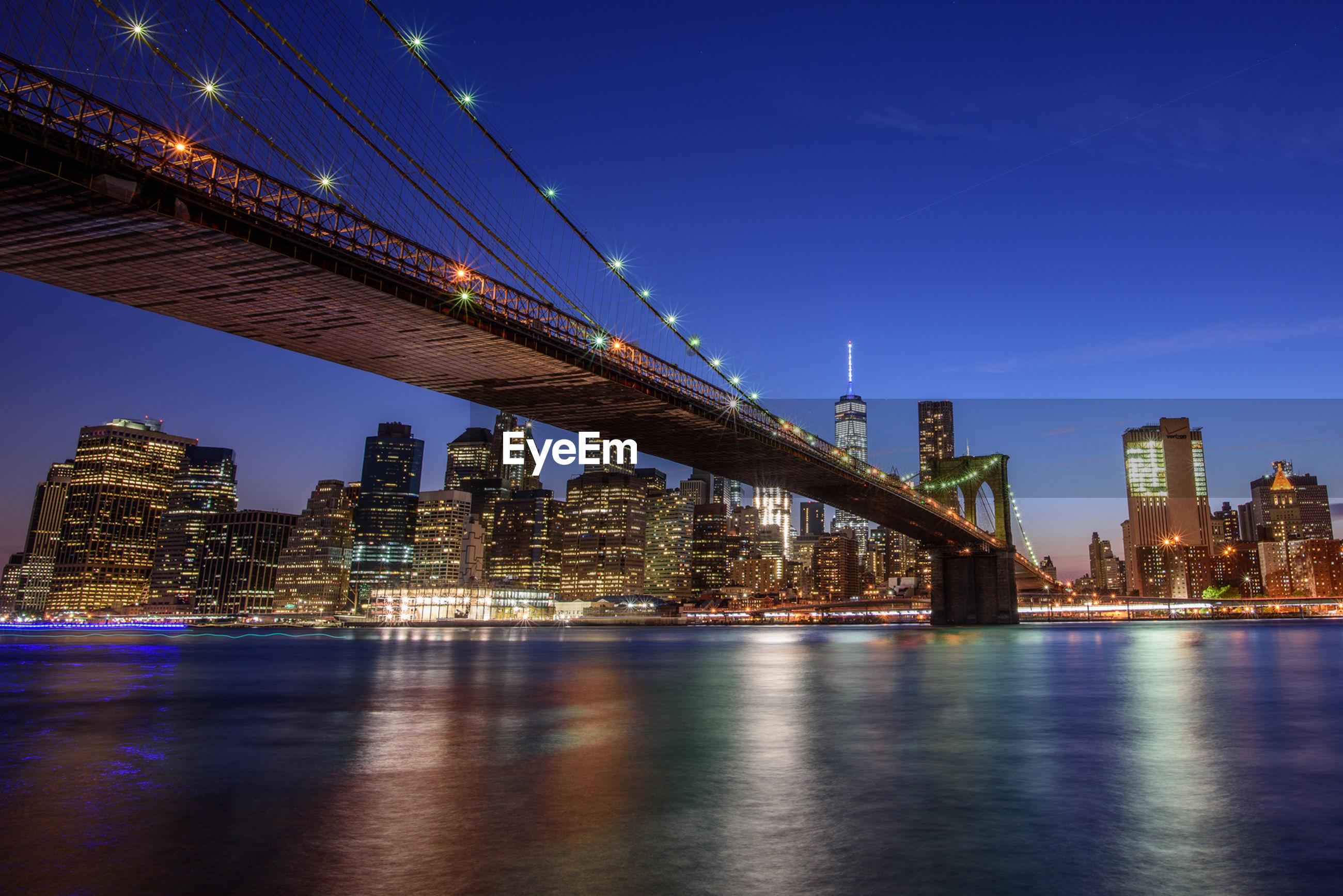 Illuminated brooklyn bridge over east river against sky