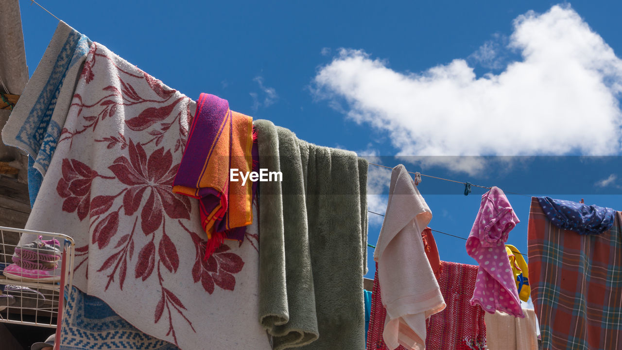 Laundries Drying On Rope Against Blue Sky