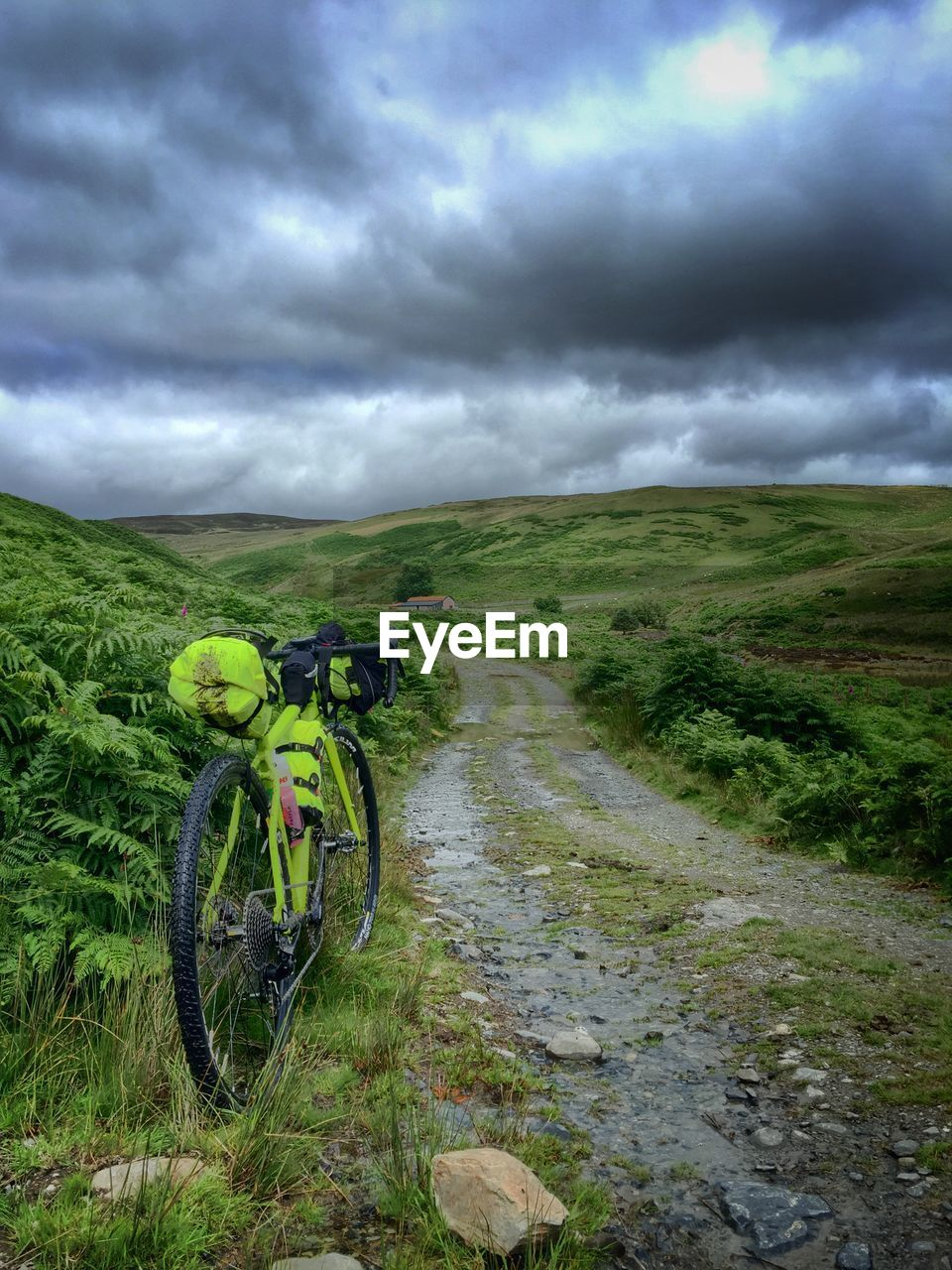 Mountain Bicycle Parked Beside Dirt Road In Dramatic Landscape