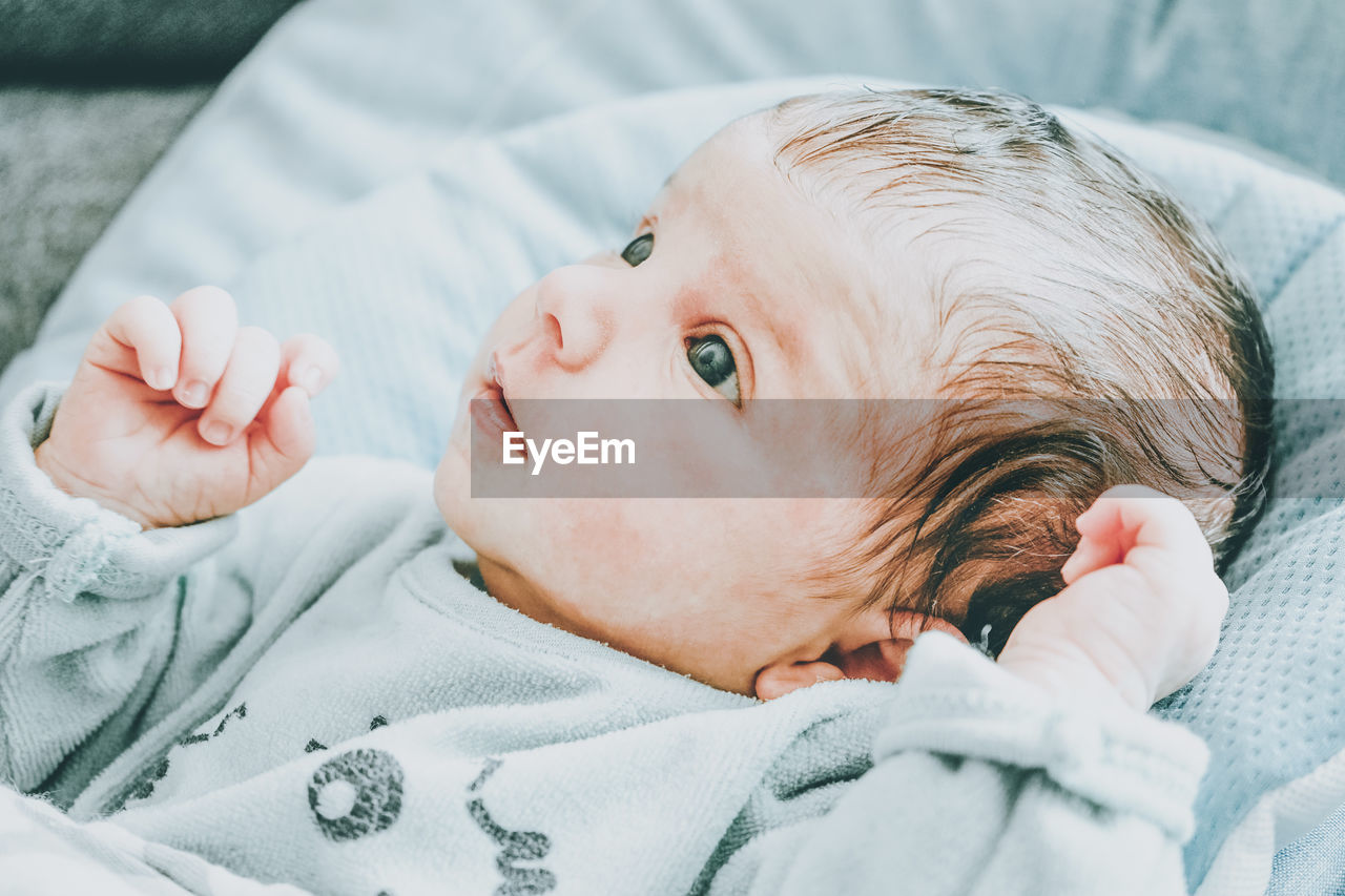 Portrait of cute baby lying on bed