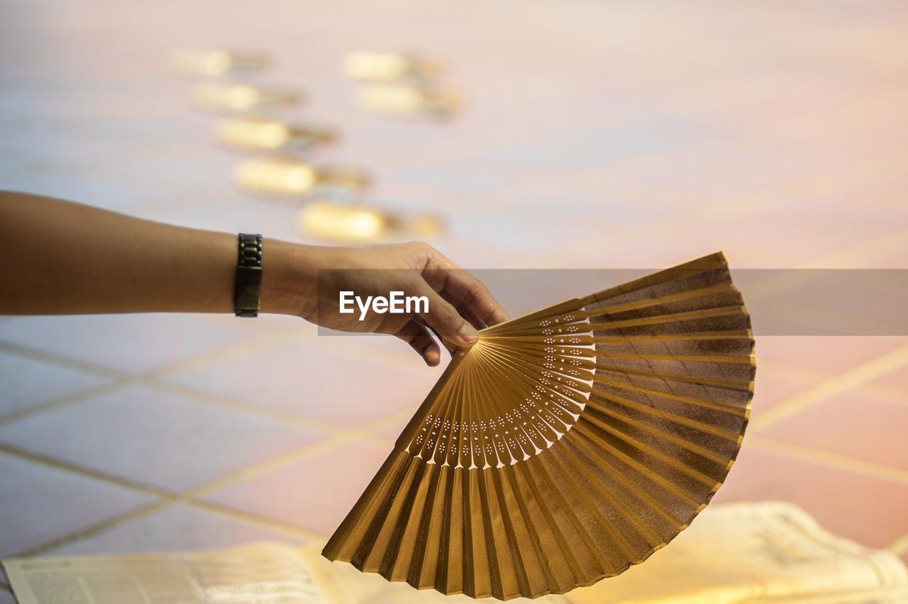 Cropped hand holding folding fan against tiled floor