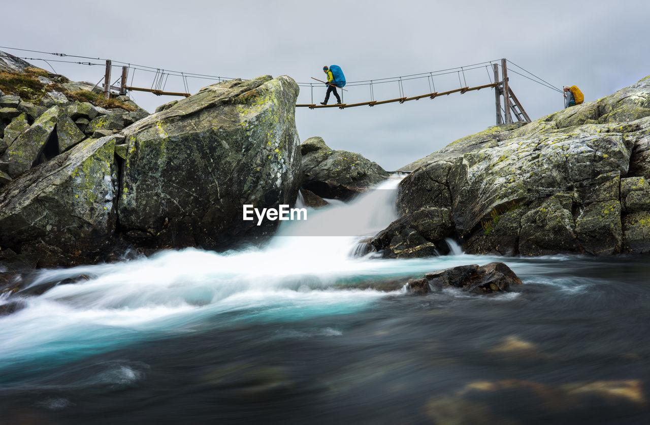 Side view of man crossing footbridge over river