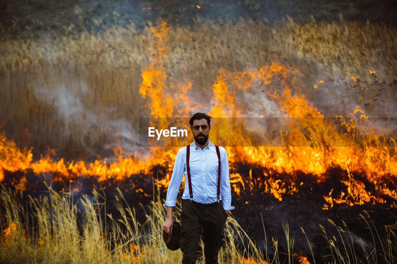 Portrait Of Man Standing On Field Against Bonfire