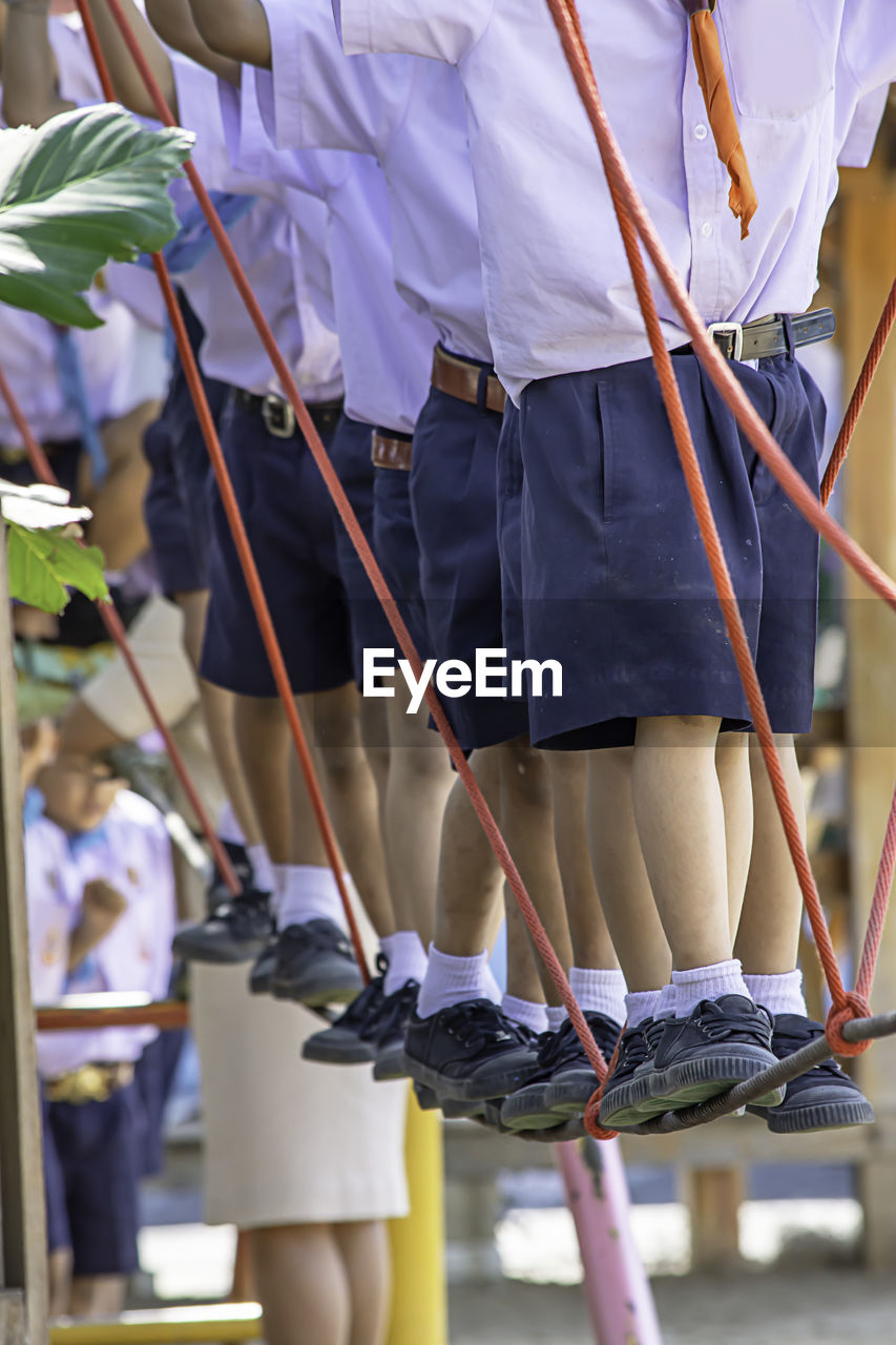 Low Section Of Students Standing On Rope At Playground