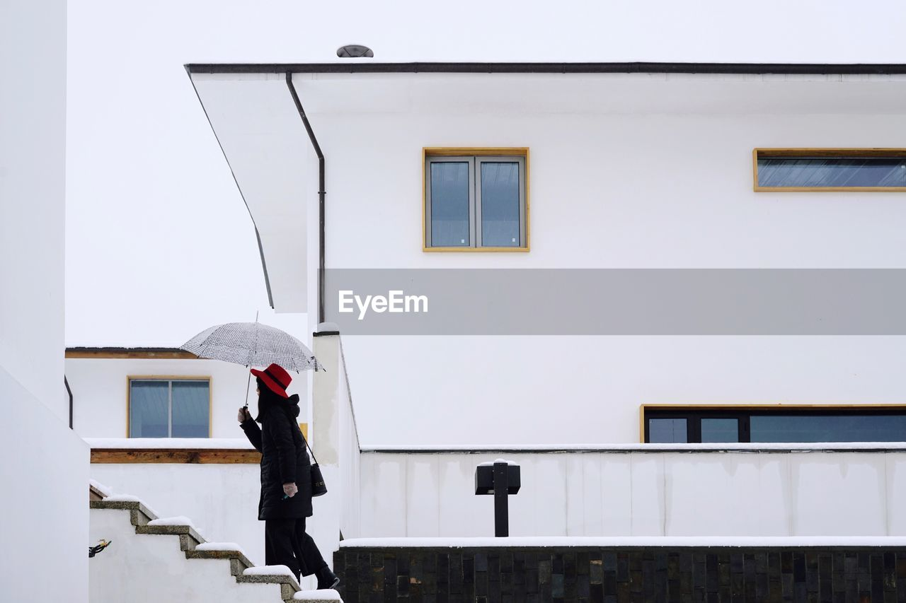 Side View Of Mid Adult Woman With Umbrella Moving Up On Steps During Winter