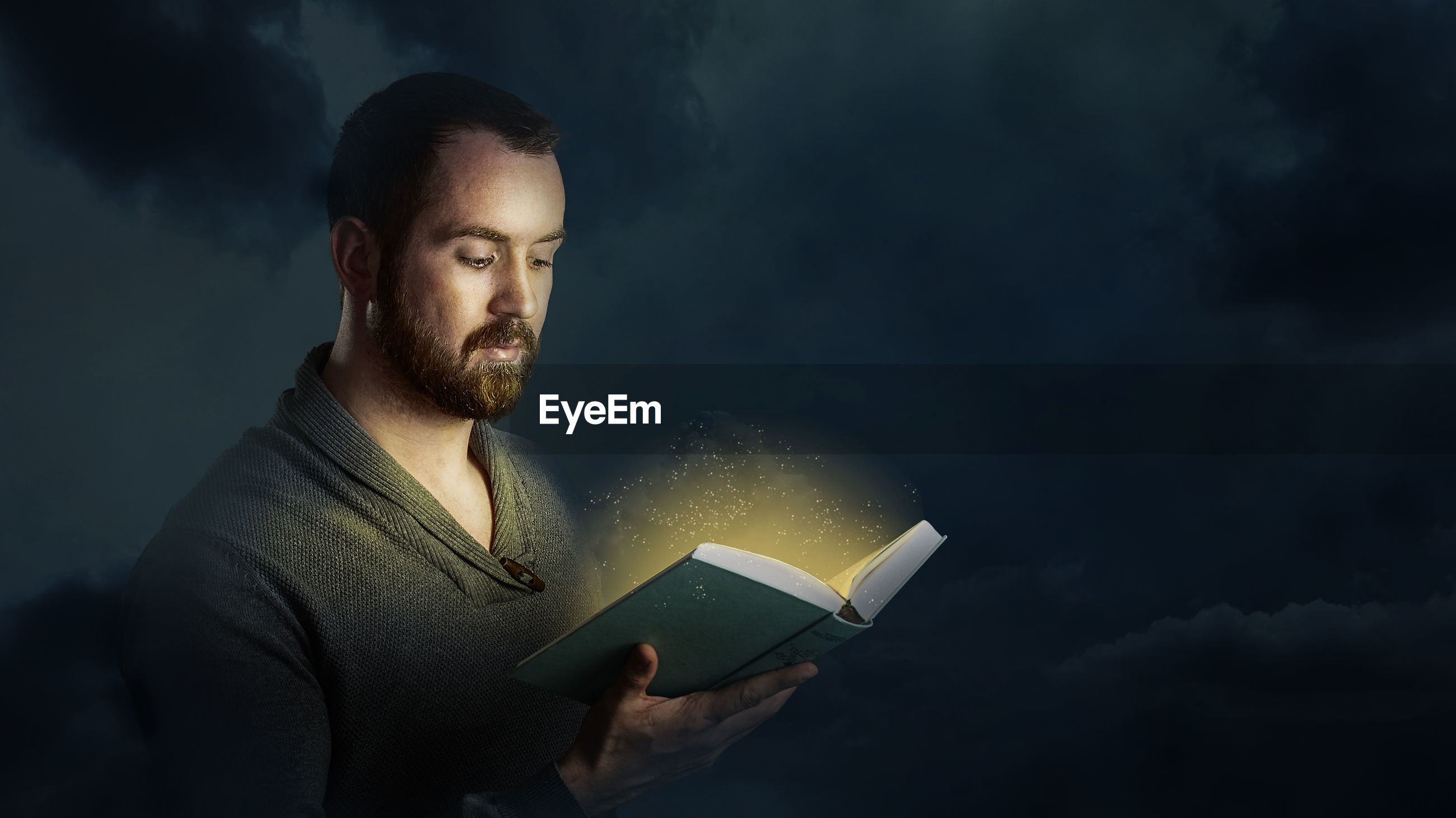 Digital Composite Image Of Man Reading Book Against Cloudy Sky At Night
