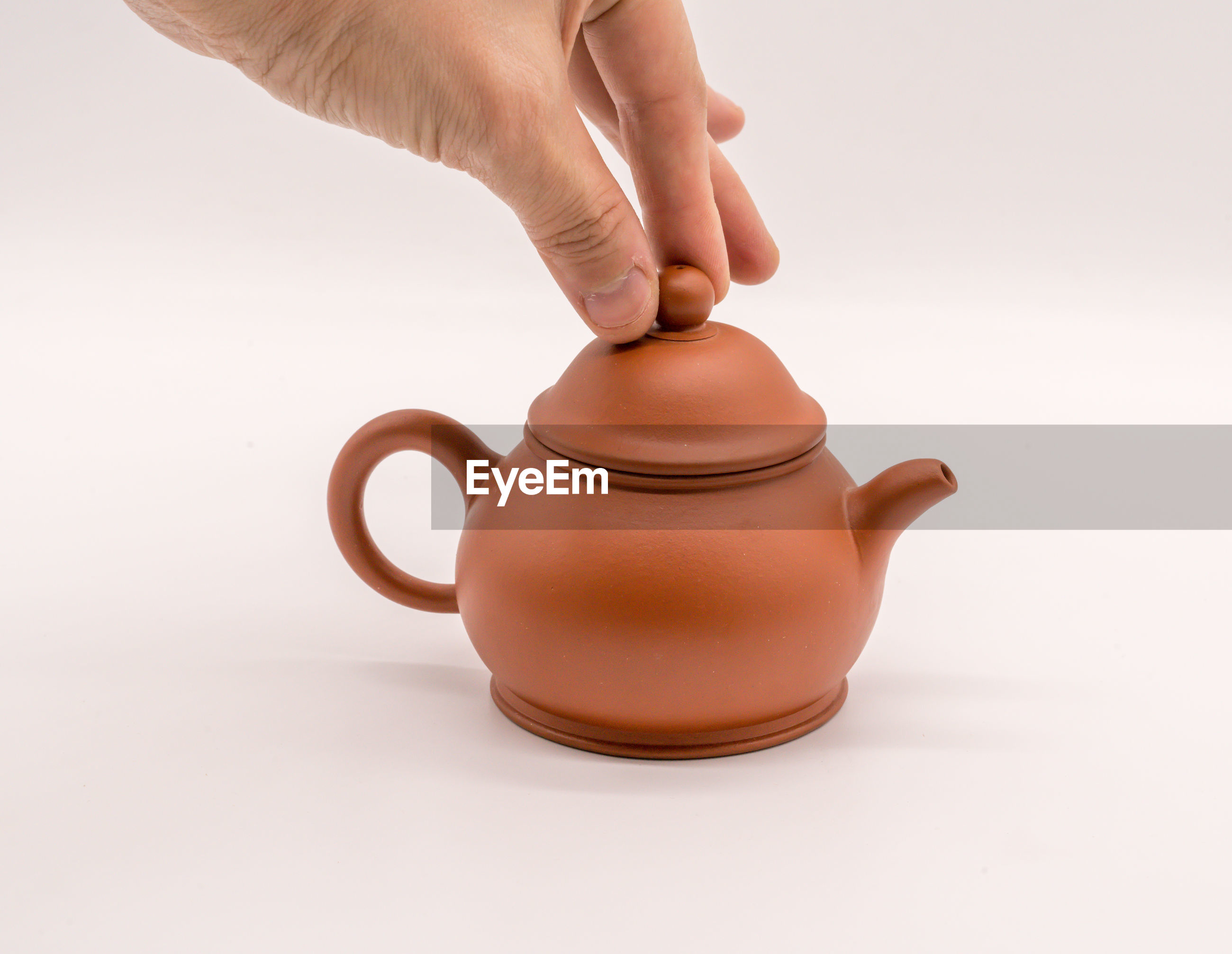 Cropped hand holding lid of teapot over white background