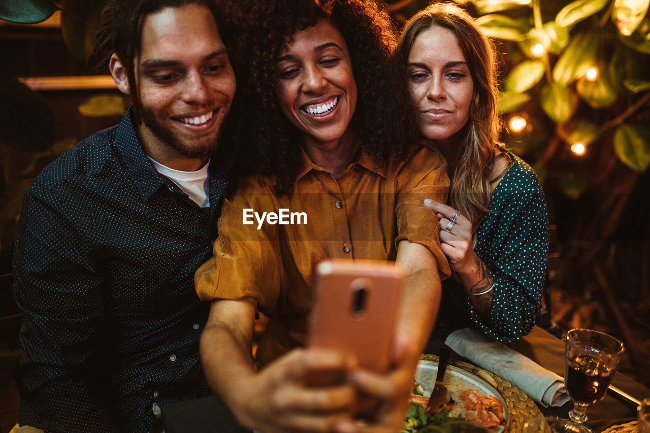 Smiling woman taking selfie with friends while sitting outdoors