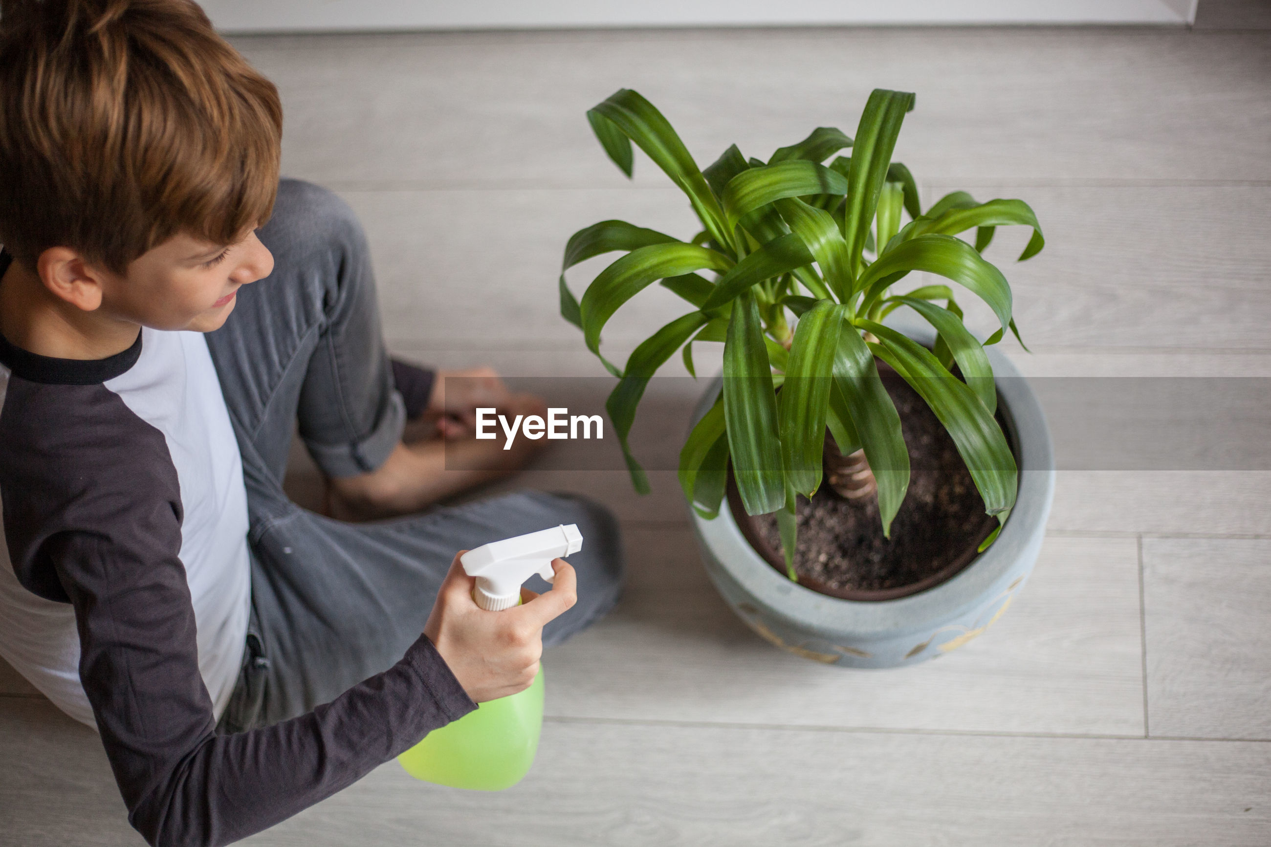 High angle view of boy watering a plant