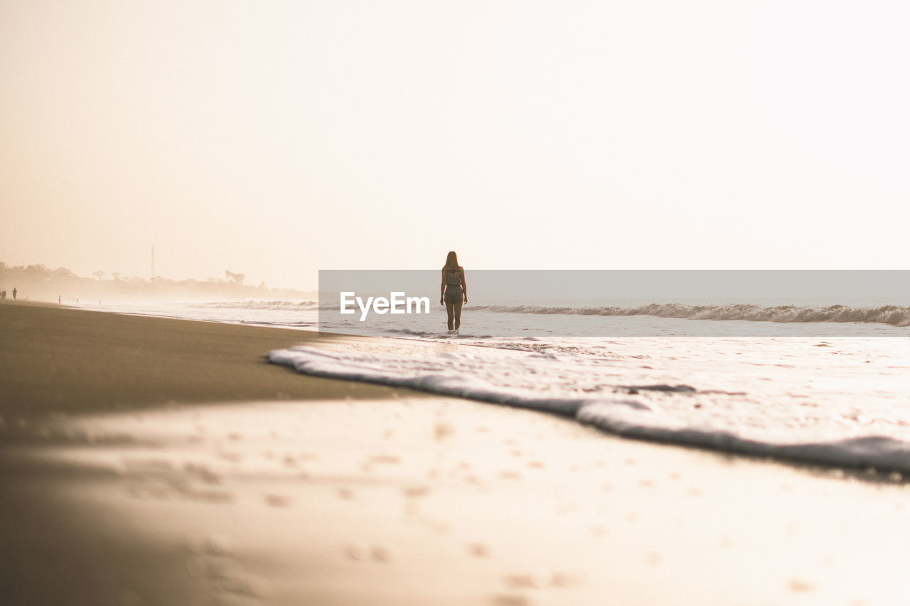 beach, land, sea, water, sky, sand, nature, copy space, real people, one person, scenics - nature, clear sky, selective focus, tranquility, leisure activity, beauty in nature, walking, horizon, outdoors, horizon over water, surface level