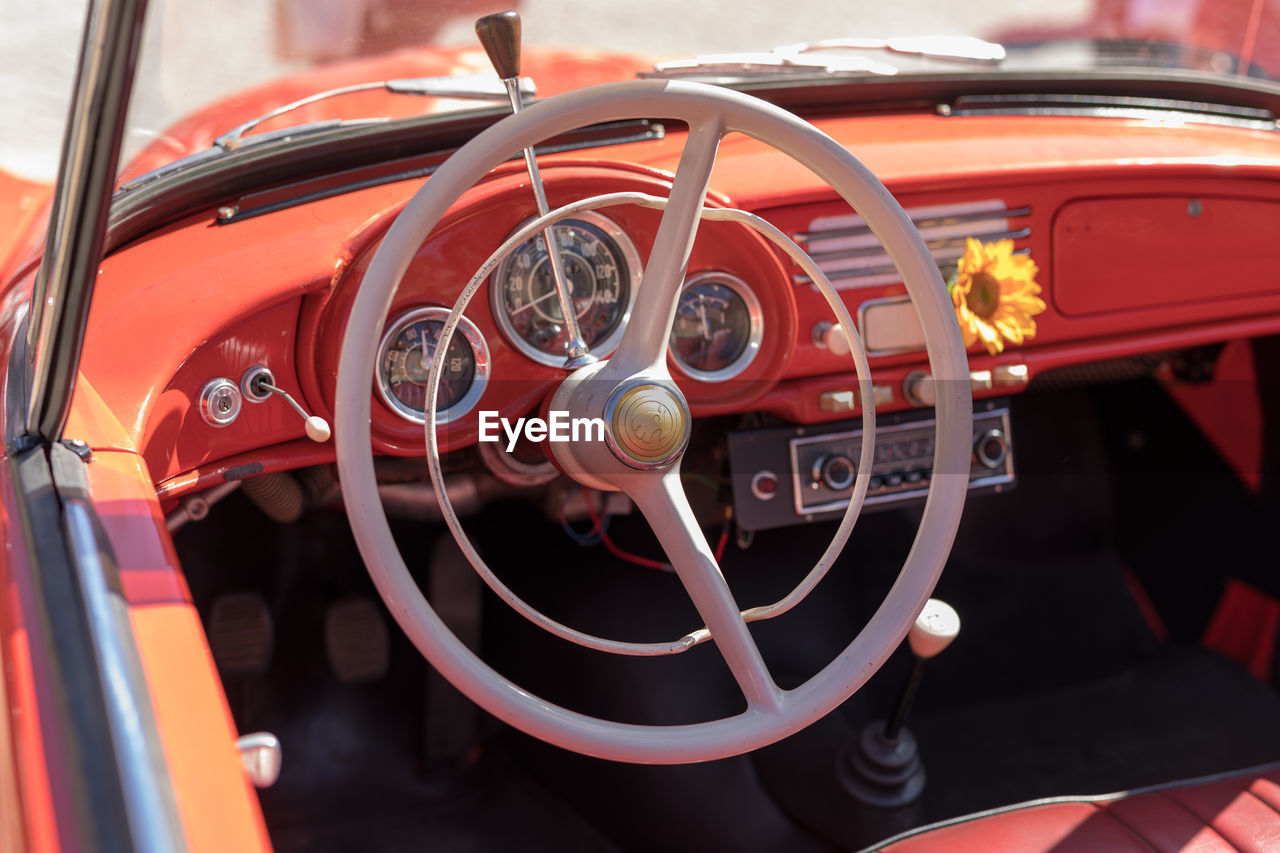 mode of transportation, car, steering wheel, transportation, land vehicle, motor vehicle, retro styled, vintage car, speedometer, control panel, dashboard, vehicle interior, close-up, red, car interior, day, no people, focus on foreground, glass - material, wheel
