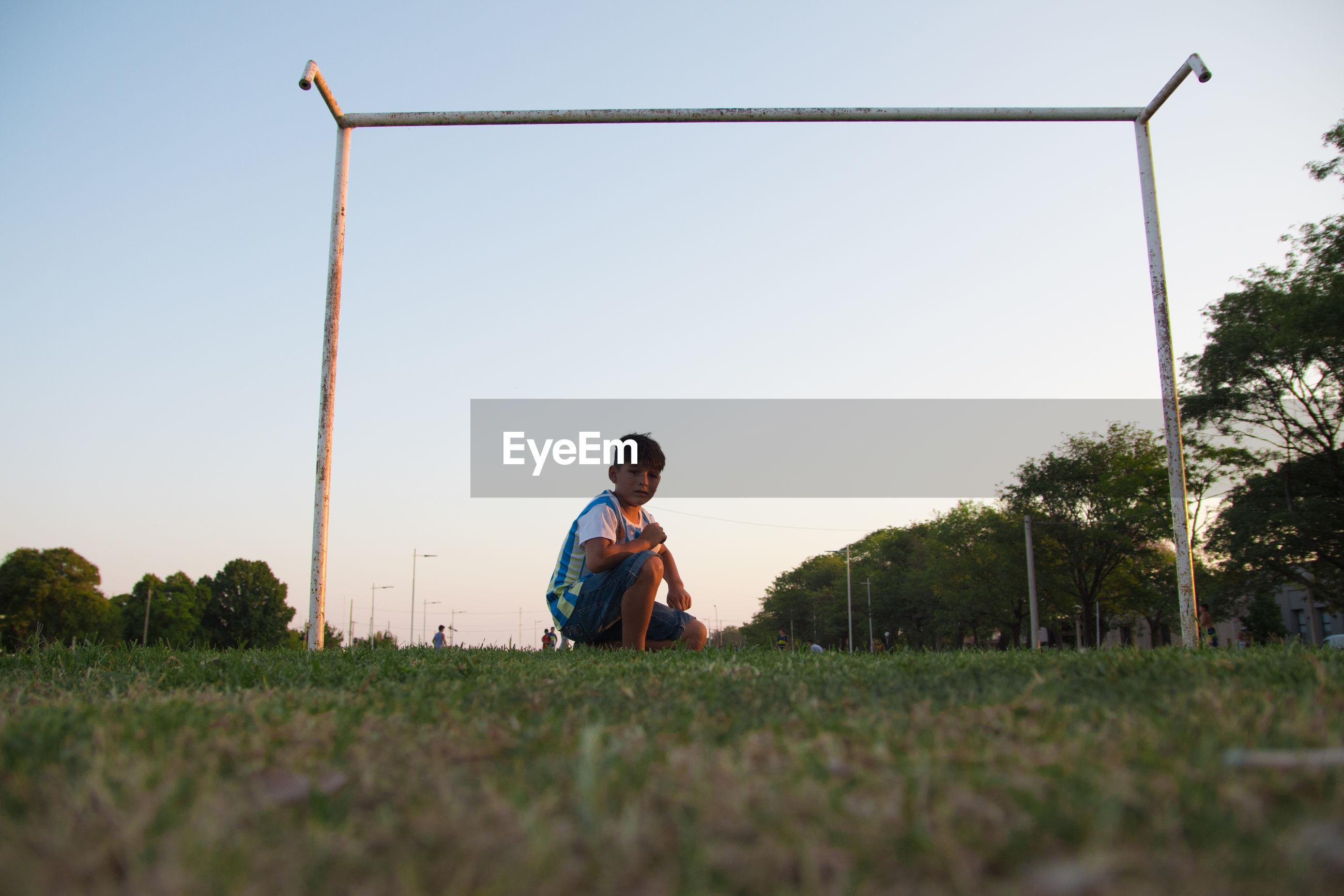 BOY SITTING ON FIELD AGAINST CLEAR SKY