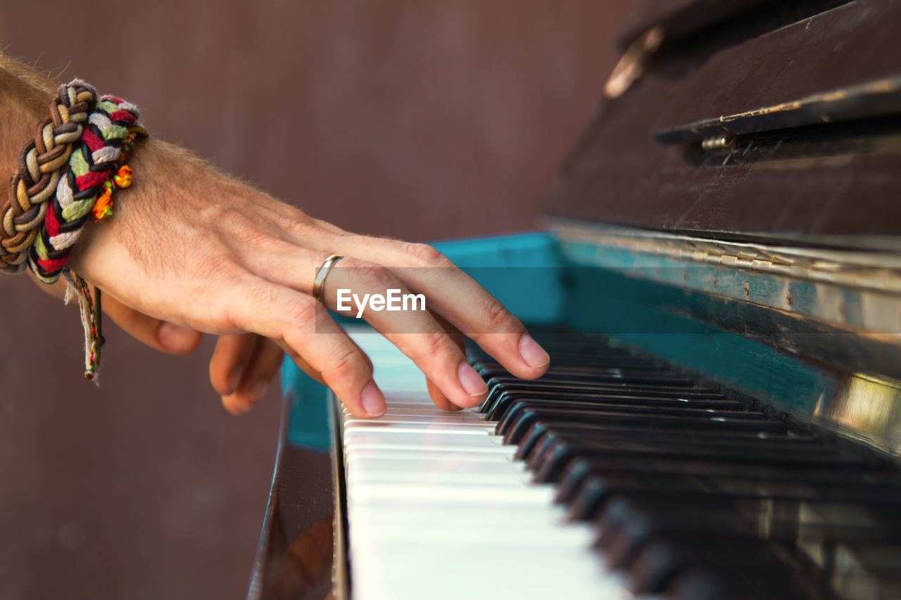 Close-up of man playing piano in home